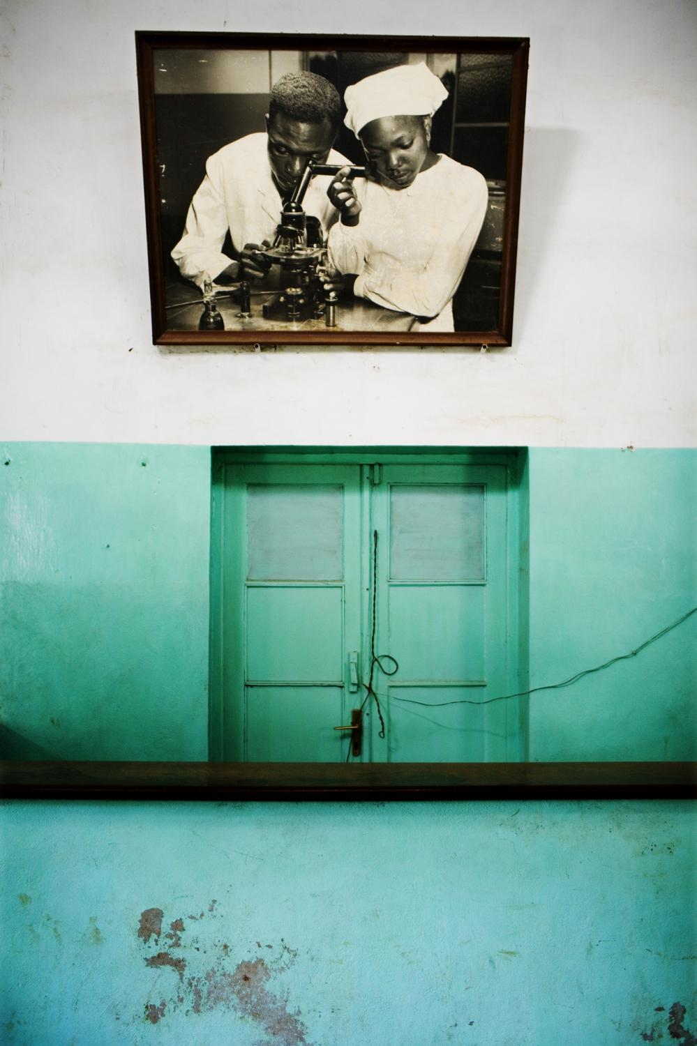 DEMOCRATIC REPUBLIC OF CONGO Bukavu, South Kivu Province An old framed photograph of a doctor and nurse looking through a microscope hangs at the entrance to Bukavu General Hospital.