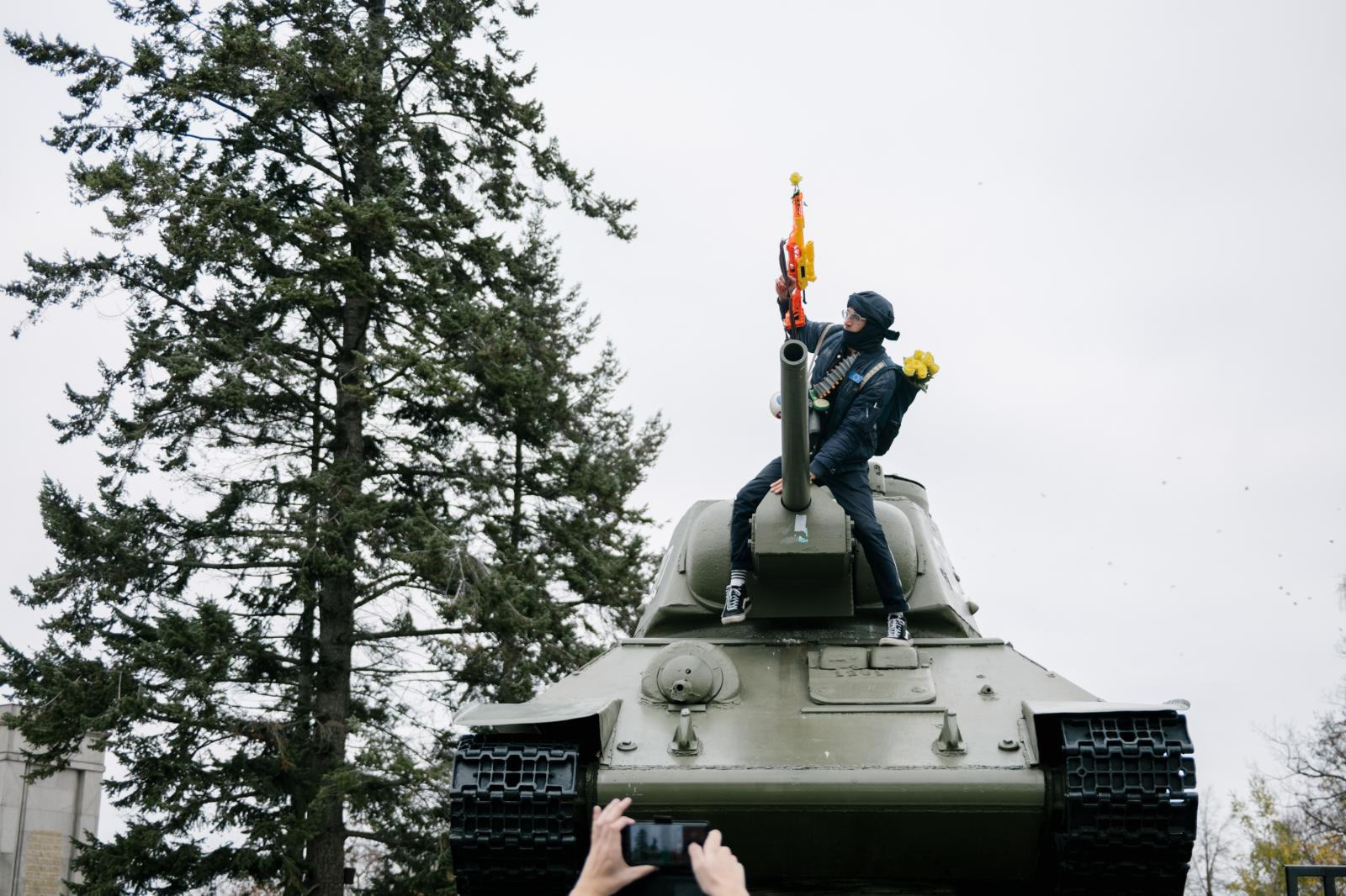 A man climbs Soviet Memorial at Strasse des 17. Juni with a plastic gun for a photo.