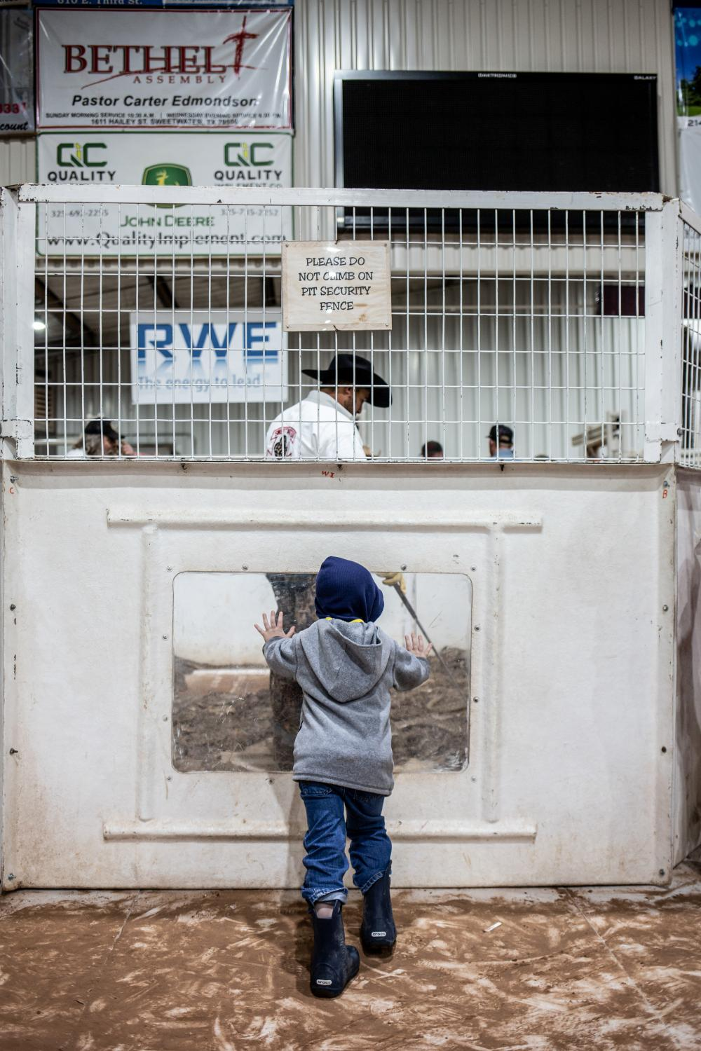 A young boy presses his hands against safety glass on the snake pit, where rattlesnakes that have been captured in the wild are brought in for slaughter.