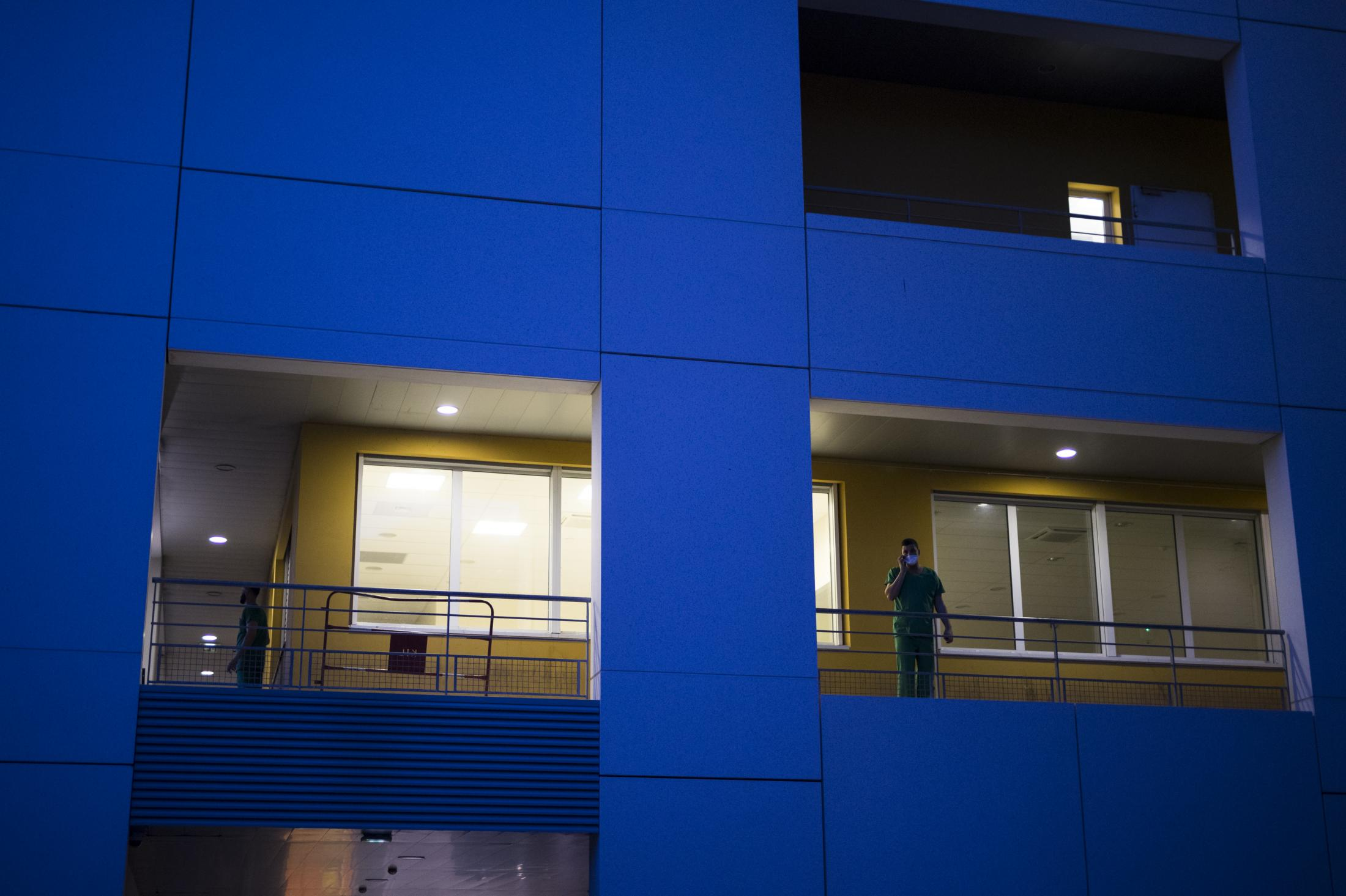 A hospital worker takes a break on an outdoor walkway as the day shift comes to an end and night falls upon the La Timone hospital in Marseille, southern France, Thursday, Nov. 12, 2020. (AP Photo/Daniel Cole)
