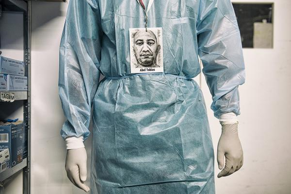 Abel Tobias Suarez Olivares, 42 year old, dressing himself before starting his daily work. When he saw how much gratitude there was in Italian patients and colleagues, he had the strength to face the exhausting working times.