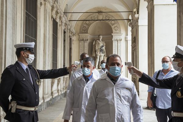 City Hall, Turin, Italy. Cuban Brigade members take the temperature before the Julio Guerra Izquierdo doctor's honorary citizenship ceremony