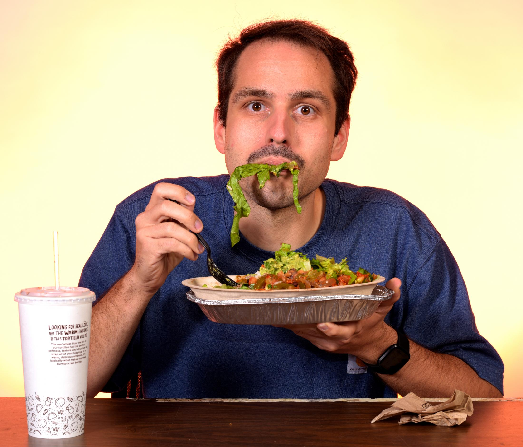 Daniel Shular eats a salad bowl from Chipotle. Shular says that Chipotle reminds him of graduate school, cheap meals and veganism.