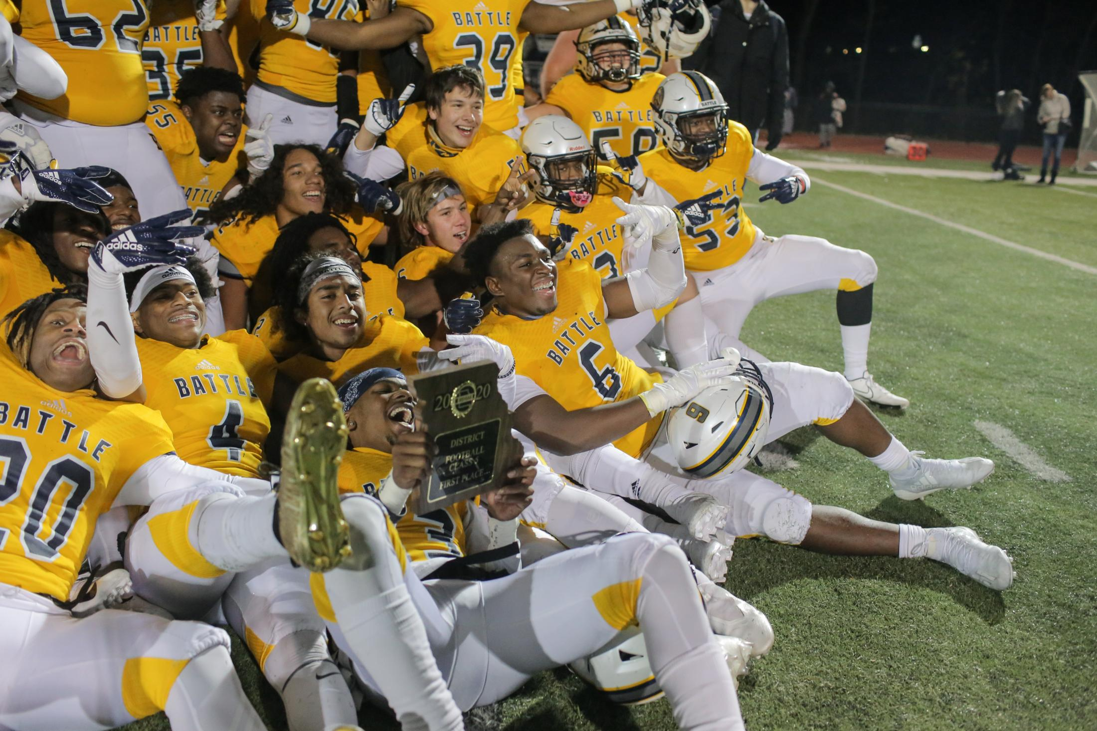 The Battle High School football team celebrates beating Washington High School and poses for photos with their Class 5 District 4 championship trophy on November 13, 2020, in Washington, MO.