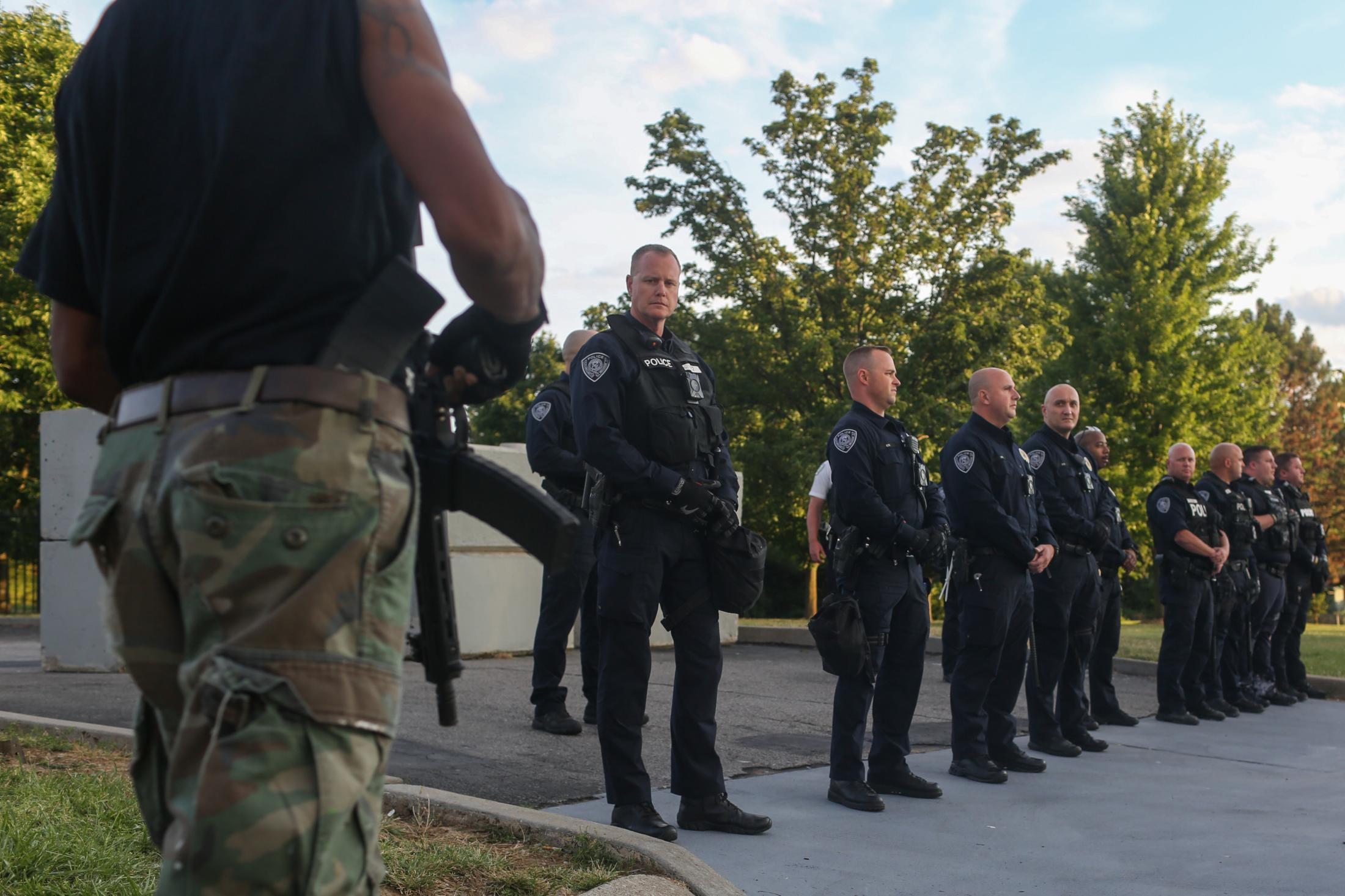 An armed protester walks in front of a line of Florissant police officers moments before shooting himself in the foot from an accidental discharge of his AR-15 on June 23, 2020, during a protest against former Florrissant officer Joshua Smith. On June 7, 2020, Smith was caught on tape hitting a man with an unmarked vehicle in the nearby municipality of Dellwood, Missouri prompting demonstrations at the police station.