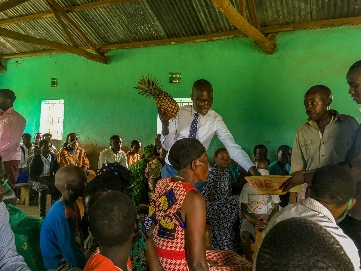 Brian Atuheire Batenda, an opposition candidate for the position of Member of Parliament for Kinkinzi West, a constituency in Kanungu District auctions a pineapple and places money into a collection basket at a fundraising event for a new classroom block organized by church youth. With only two congregants putting on masks and zero social-distancing being observed, this scene offers insight on both the candidate and voter's take regarding the basic guidelines issued by the Electoral Commission.