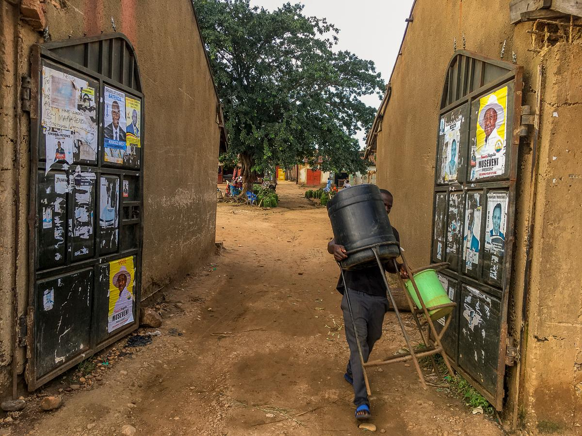 A man carries a handwashing setup past the entry point of Kihihi Town Council Market in Kanungu district, early in the morning before the market (whose gate is covered with campaign posters) opens and is flocked by the public. This young man refills the setup with water and soap every morning and makes sure it does not run out through the course of the day. Hand washing seems to be the most respected guideline regarding the COVID-19 SOPs in most public spaces within Kihihi Town.