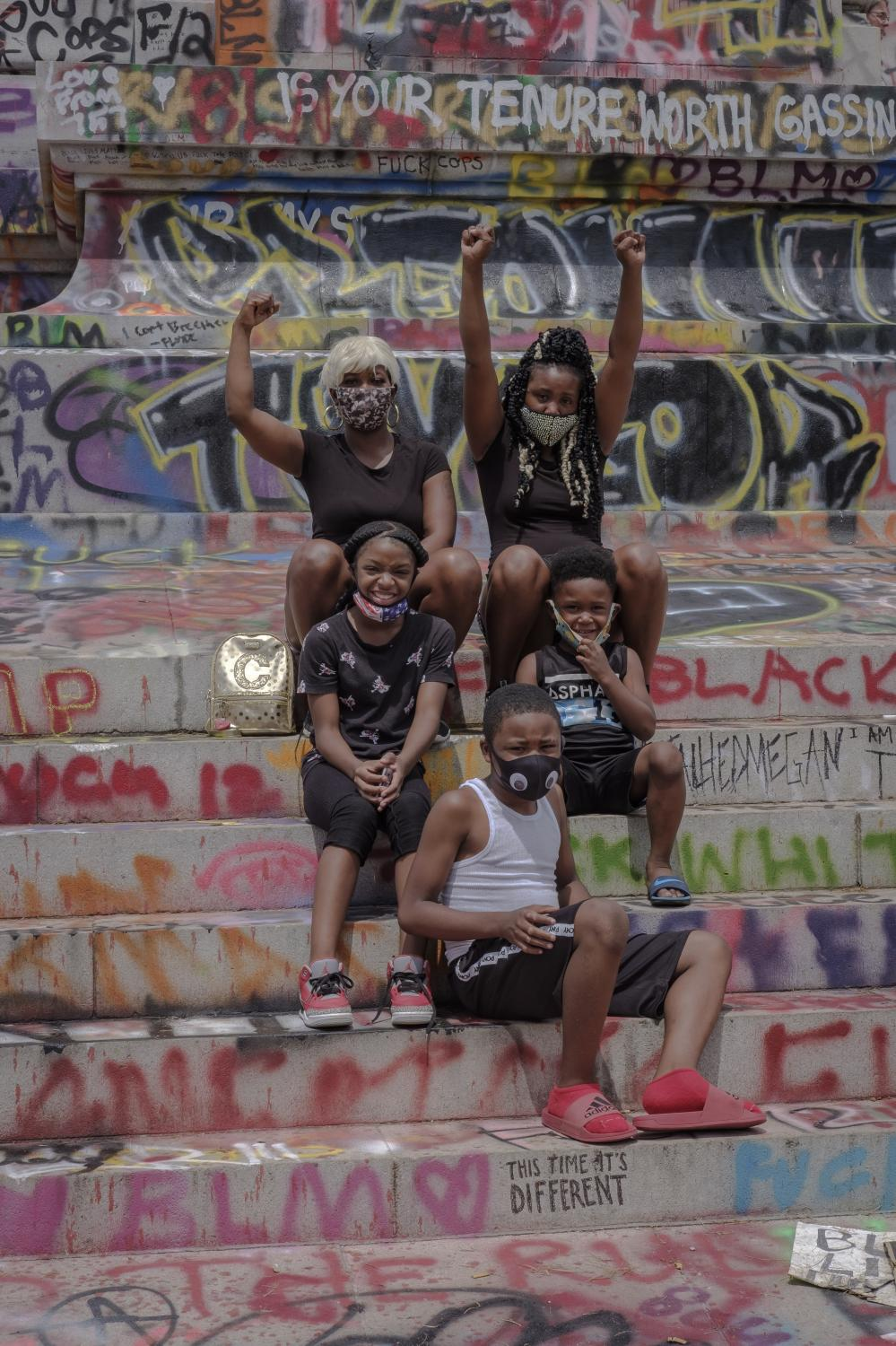"""RICHMOND, VA - June 20, 2020: Kimberly Coward, her sister Danielle Coward and their kids pose for a portrait at the Robert E. Lee Monument on June 21, 2020. To celebrate the """"Juneteenth,"""" Richmond residents gather at Monument Avenue to honor those who have been killed by police officers and to protest police brutality. The monument has been claimed by the community and has become a healing space where parents take photos with their children, play basketball and share a meal on the now proclaimed """"Marcus-David Petters Circle"""". The Robert E. Lee memorial has been renamed in honor of the young Marcus-David Petters, who was shot and killed by a Richmond police officer on May 14, 2018. Photo: Carlos Bernate for The New York Times."""
