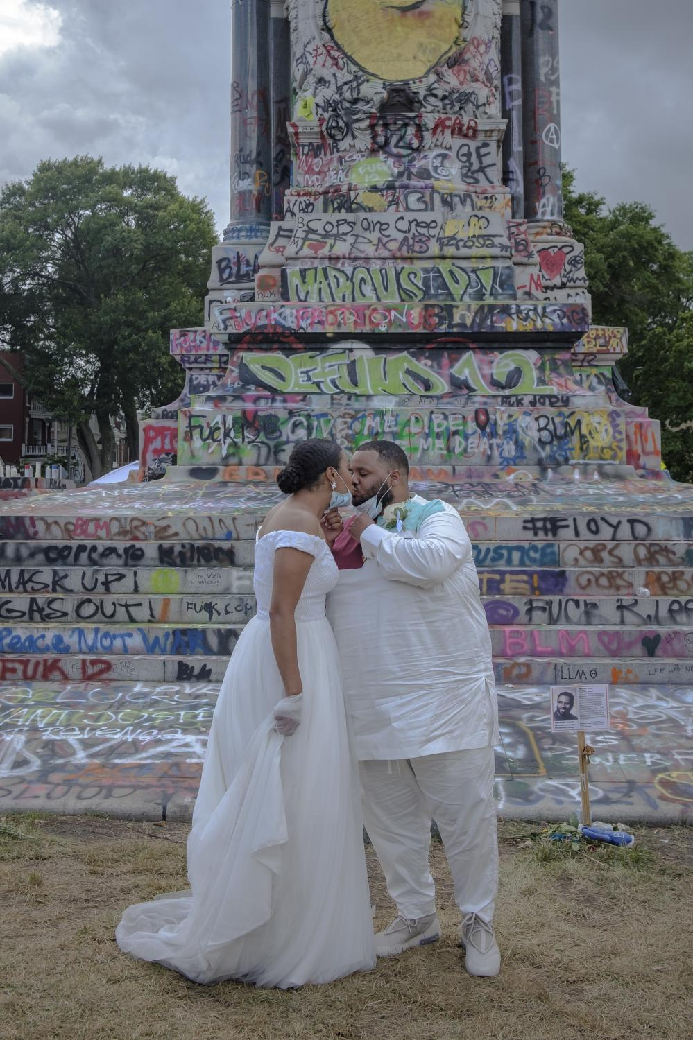 """RICHMOND, VA - June 20, 2020: Bride Chaela Wilson and groom Marcus Wilson kiss at the Robert E. Lee Statue on June 21, 2020. To celebrate the """"Juneteenth,"""" Richmond residents gather to honor those who have been killed by police officers and to protest police brutality on June 21, 2020 at Monument Avenue. The monument has been claimed by the community and has become a healing space where parents take photos with their children, play basketball and share a meal on the now proclaimed """"Marcus-David Petters Circle"""". The Robert E. Lee memorial has been renamed in honor of the young Marcus-David Petters, who was shot and killed by a Richmond police officer on May 14, 2018. Photo: Carlos Bernate for The New York Times."""