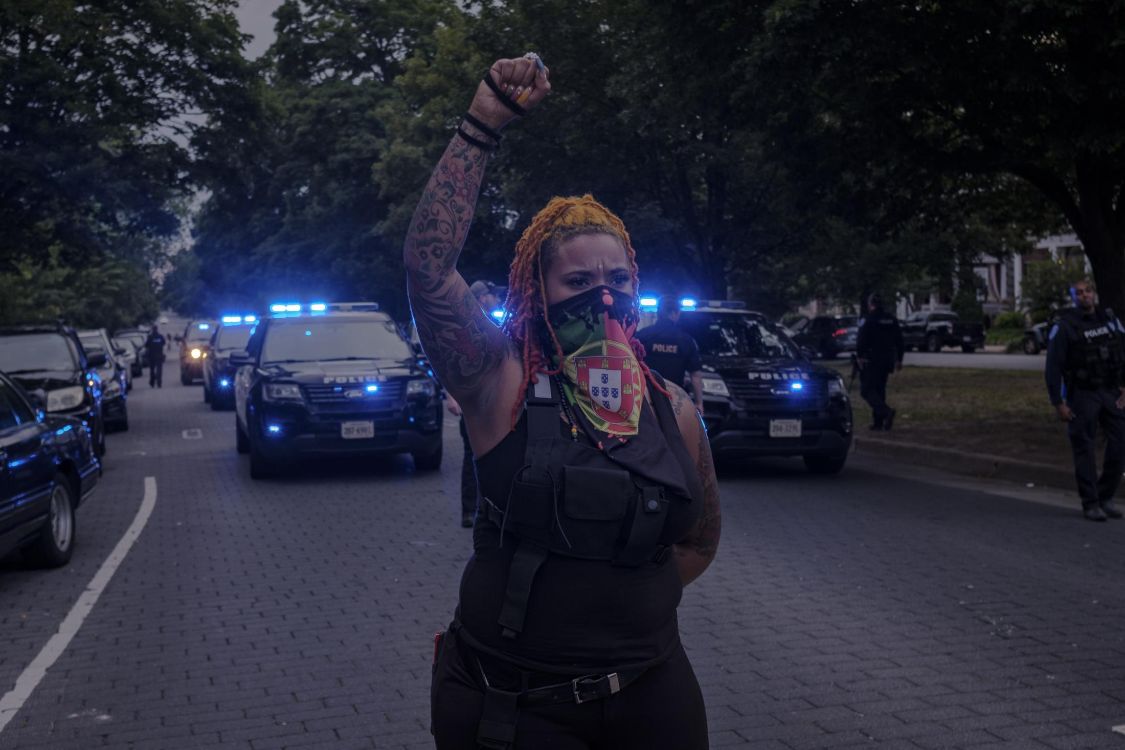 """RICHMOND, VA - June 20, 2020: Richmond police arrive heavily-armed at the Robert E. Lee memorial and require the participants to disperse the area. To celebrate the """"Juneteenth,"""" Richmond residents gather to honor those who have been killed by police officers and to protest police brutality on June 21, 2020 at Monument Avenue. The monument has been claimed by the community and has become a healing space where parents take photos with their children, play basketball and share a meal on the now proclaimed """"Marcus-David Petters Circle"""". The Robert E. Lee memorial has been renamed in honor of the young Marcus-David Petters, who was shot and killed by a Richmond police officer on May 14, 2018. Photo: Carlos Bernate for The New York Times."""