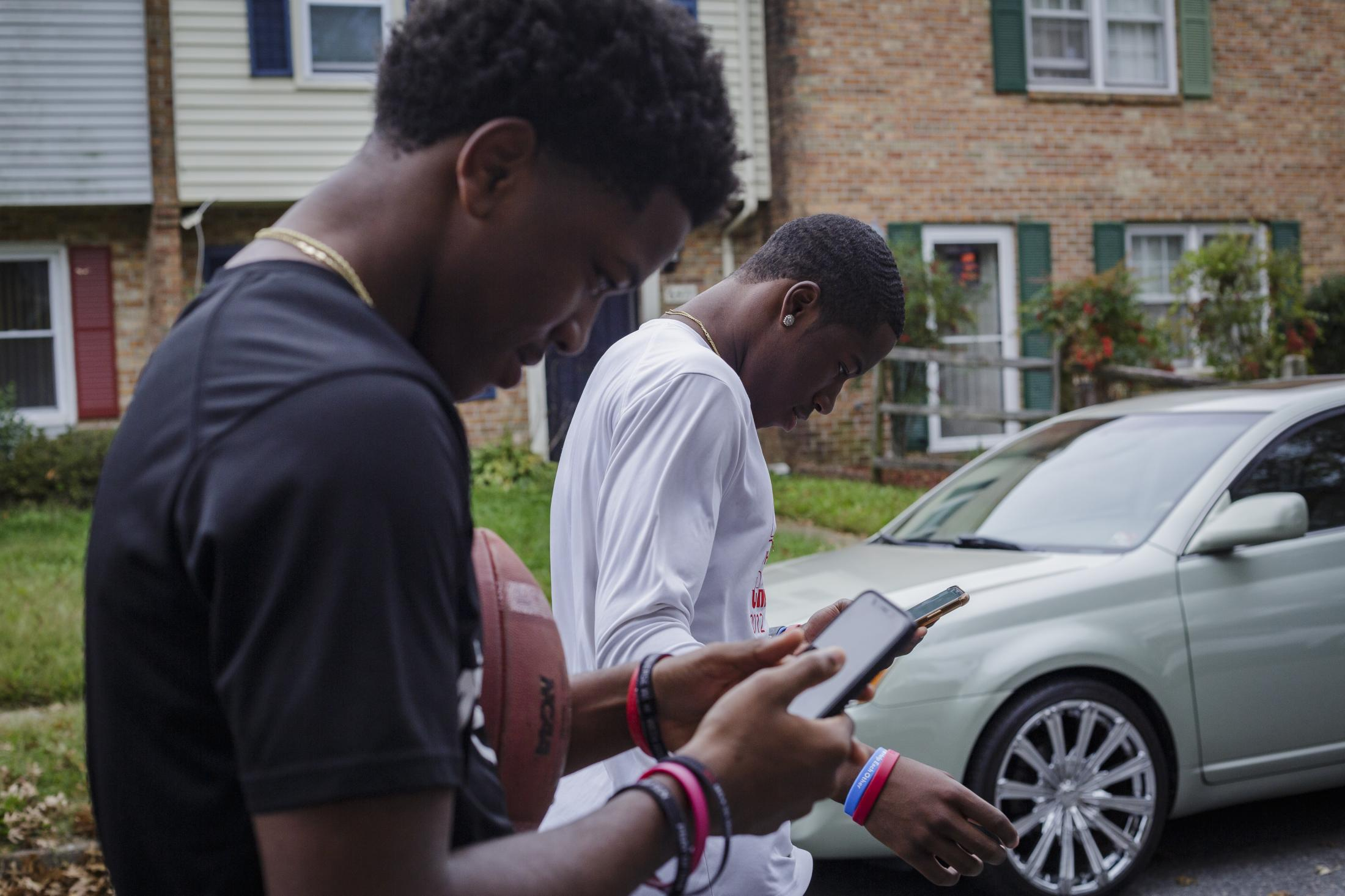 NORFOLK, VA – October 29, 2020: Pierre Royster and Jeff Foster, members of the Lake Taylor High School TITANS, walking around their neighborhood while watching videos on their phones. Due to the COVID-19 pandemic, football games were canceled at Lake Taylor High School in Norfolk, VA, leaving the TITANS members with plenty of free time. Carlos Bernate / The Undefeated