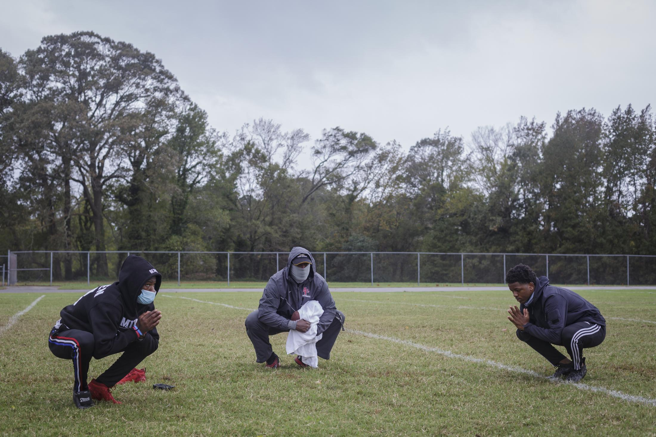 NORFOLK, VA – October 29, 2020: Jeff Foster (left), Assistant Coach Antonio Thompson (Center) and Pierre Royster (right) members of the Lake Taylor High School TITANS, at football practice during a warm-up. Due to the COVID-19 pandemic, football games were canceled at Lake Taylor High School in Norfolk, VA, but weekly practice are still going on. Carlos Bernate / The Undefeated
