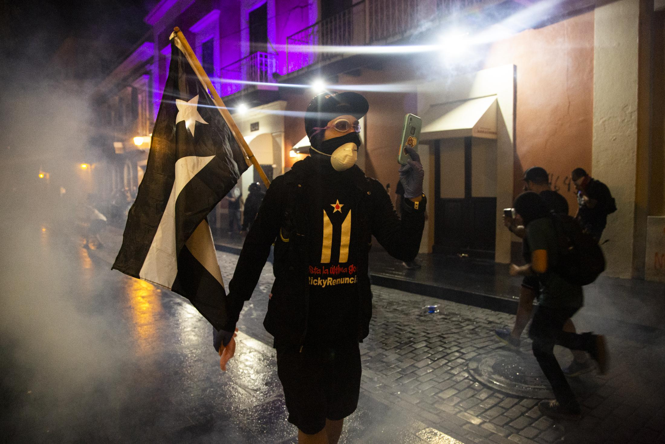 A protester records a riot police formation after teargas had been shot. Clashes erupted outside the governor�s mansion during a protest to demand the resignation of governor Wanda Vazquez Garced in San Juan, P.R., on Thursday, January 23, 2020. Last Saturday a storage with aid from hurricane Maria was found with undistributed supplies in Ponce, an area affected by the recent earthquakes. The protest today was called on by unions, artist Rene Perez Joglar, known as Resident, and baseball player, Yadier Molina. (Erika P. Rodriguez for The New York Times)