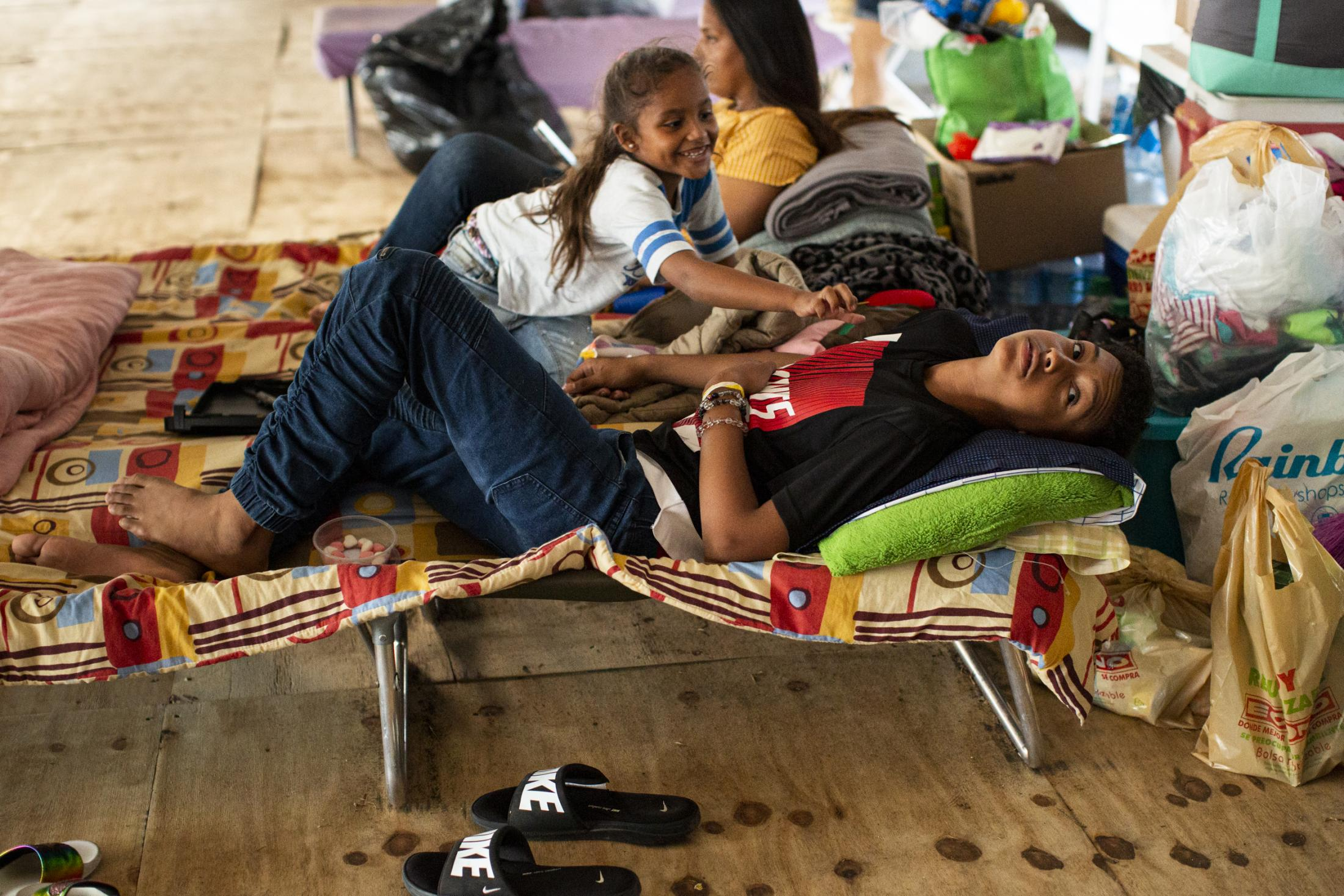 Keythens Martinez Ramirez, 12, with his sister and mother, Irmarie Ramirez Santiago, 27, and Irmarilys Torres Ramirez, 6, at their living area in the shelter based in the town's athletics track in Guanica, P.R., on February 13, 2020. The family, whose house was damaged in the earthquake, has been between shelters since Jan 7. After a cluster of earthquakes ravaged the south of the island last month 800 people are still living in government shelters and makeshift camps. Hundreds are thought to be camping in their backyards In fear of having their homes collapse if another mayor quake hits. On January 7 the strongest earthquake hit at a 6.4 magnitude. (Erika P. Rodriguez for The New York Times)