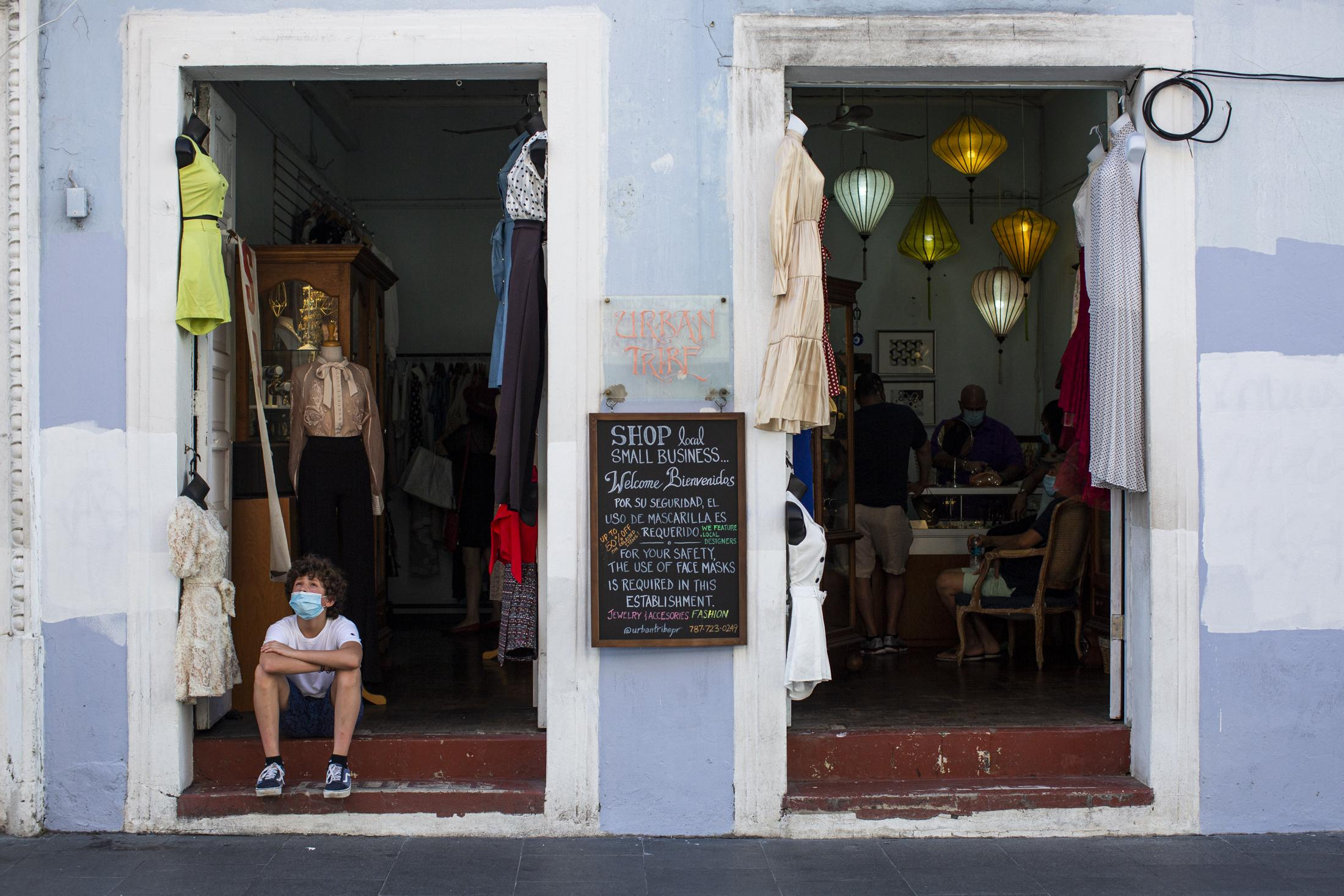 NYTVIRUS - A boy sits at the entrance of a store in Old San Juan, San Juan, P.R., on August 13, 2020. People in the Old San Juan community reported issues with tourists not wearing masks while in the area after the island opened itself for tourism. Almost 300 people have died from the Covid-19 pandemic on the island. (Erika P. Rodriguez for the New York Times)