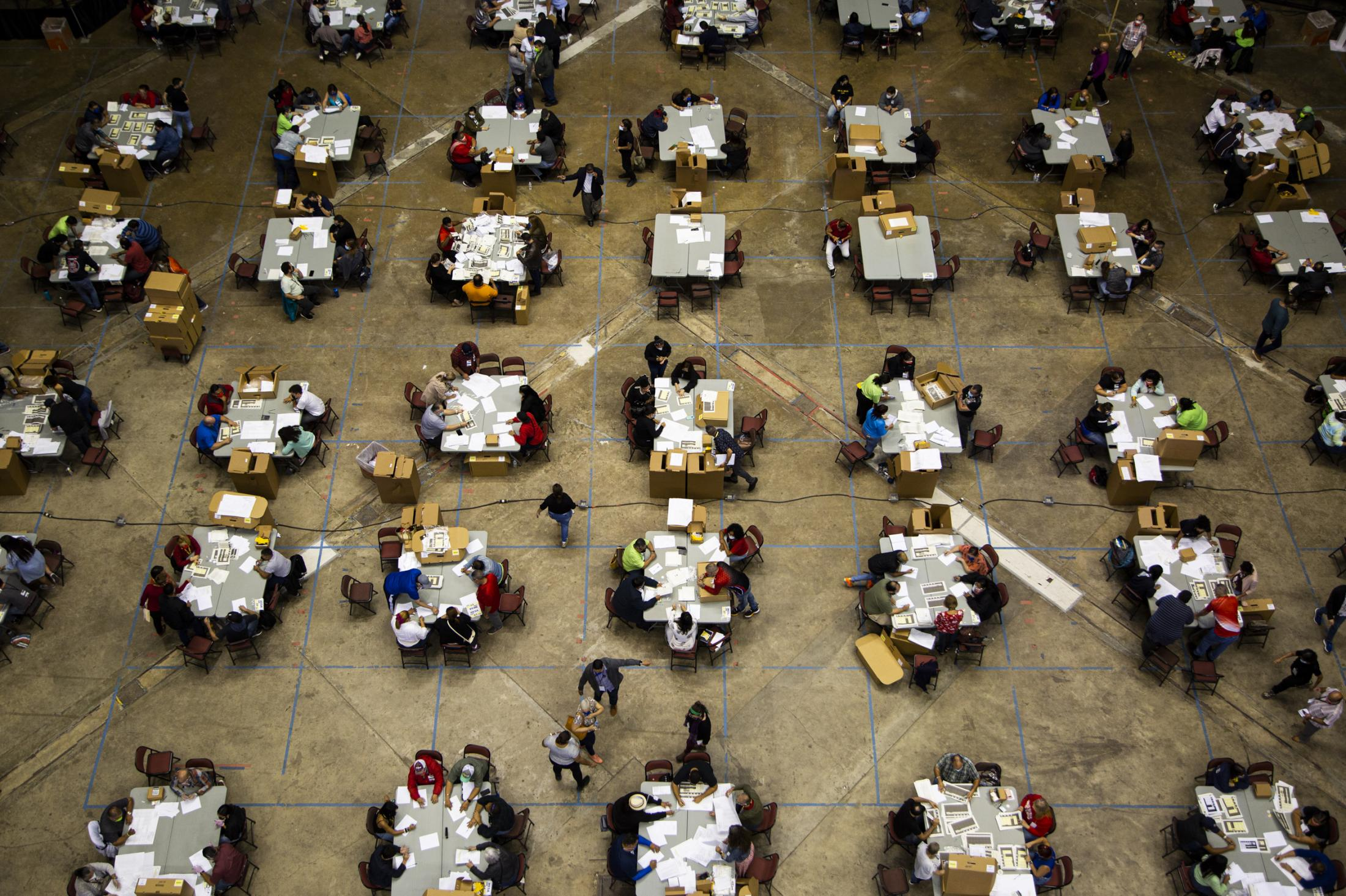 The boxes of ballots that were recently found are counted at the Roberto Clemente Coliseum in San Juan, P.R., on Nov. 11, 2020. A week after the island's general election 125 boxes of uncounted votes surfaced. At each table representatives from each main party are to be present in the count. (Erika P. Rodriguez for the New York Times)