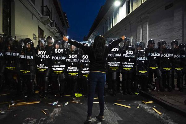 A demonstrator faces a police squad blocking Sebastian de Benalcazar Street, blocking the pass of the protest in its way to the presidential palace, to claim against the measures imposed by the government,in downtown Quito on the afternoon of September 17, 2014. Quito, Ecuador.