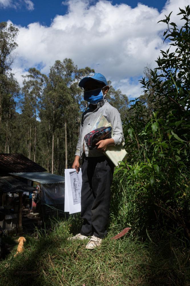 Alexander Venegas (9) camino a casa de unos familiares quienes le ayudan a realizar sus tareas mientras su madre está en su trabajo en una hacienda. Todas las mañanas Alexander lleva consigo sus lápices, cuadernos, sus guías impresas y su tapabocas para moverse de su casa a la casa de sus parientes, que se encuentran a menos de un kilómetro de distancia. 26 de mayo de 2020. Cotogchoa-Ecuador. Andrés Yépez. La cotidianidad en las zonas rurales ha sido afectada de diferente manera que en las zonas urbanas. Su confinamiento no se limita a estar dentro de casa. El campo es parte de su casa. Alexander Venegas (9) is on his way home from relatives who help him with his chores while his mother is at work on a hacienda. Every morning Alexander takes his pencils, notebooks, printed guides and his mask with him to move from his house to the house of his relatives, who are less than a kilometer away. May 26, 2020. Cotogchoa-Ecuador. Andrés Yépez. Daily life in rural areas has been affected differently than in urban areas. Their confinement is not limited to being inside the house. The countryside is part of their home.