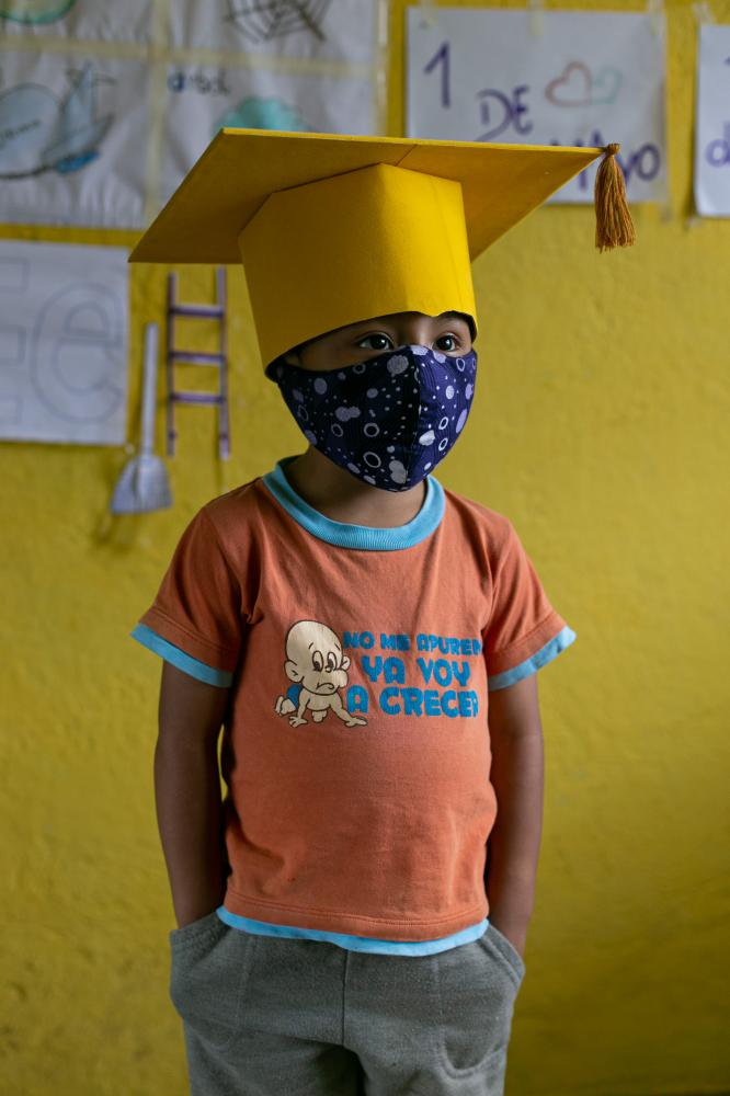Gael Pin (4) wears the cap and mask he will use at the closing ceremony of the school year, which will be done via video conference. Gael's family doesn't have internet service because of money but fortunately his neighbor has that service and shares it with them. June 18, 2020. Cotogchoa-Ecuador. Andrés Yépez.