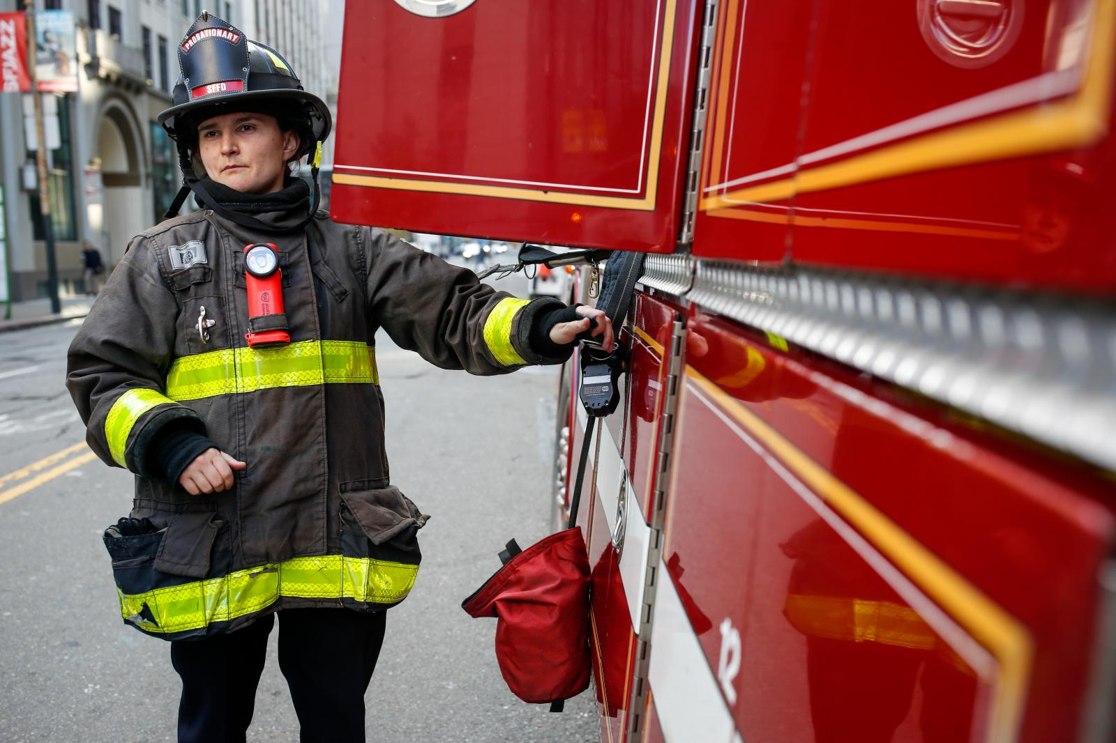 Probationary firefighter, Sasha Trofimova, performs a routine safety check on truck 13 outside of fire station 13.
