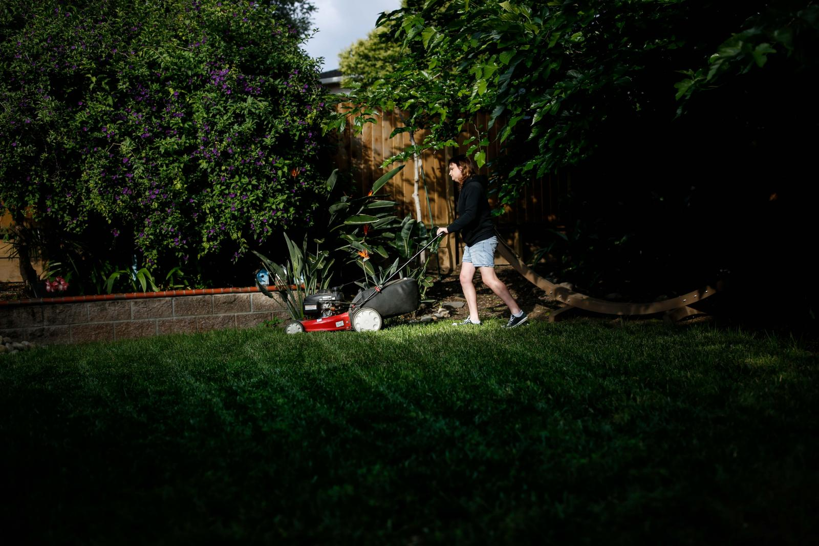 Pia Cruz, 22, mows the lawn at her parent's home on Thursday, May 24, 2019 in San Jose, Calif.