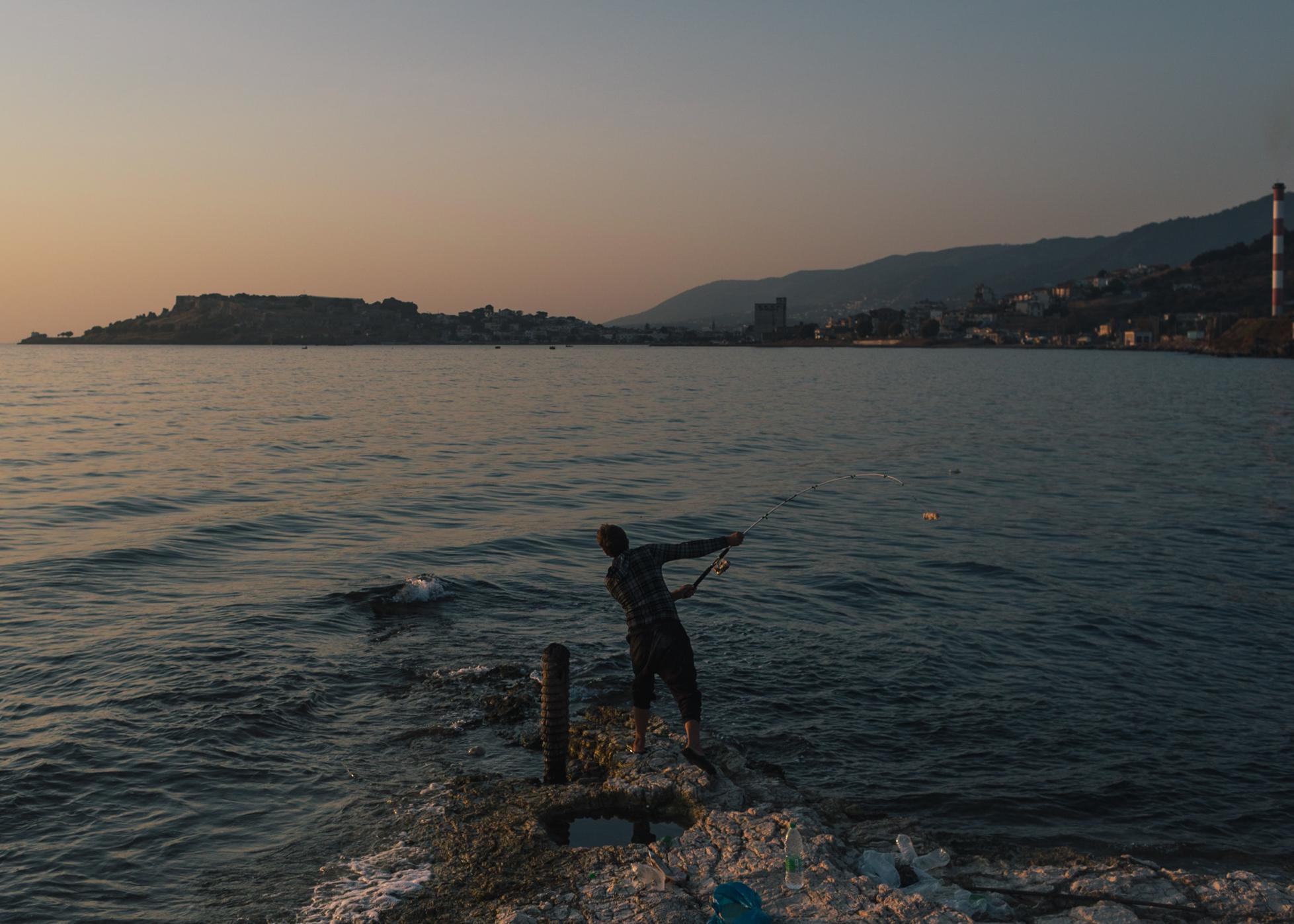 Ohab aus Kunduz in Afghanistan fischt am frühen Morgen Fische im Meer. Nachdem er fast anderthalb Jahre auf der Insel gewartet hat, hofft er nun bald den Termin für sein Asylinterview zu bekommen.