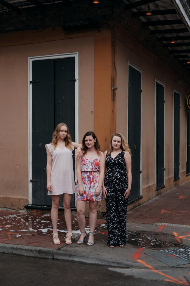 Tulane students Isabella Smith, 22, Maggie O�Donnell, 22, and Shea Jolly, 21, pose for a portrait before taking graduation pictures in the French Quarter on March 19, 2020. (Annie Flanagan for The New York Times)