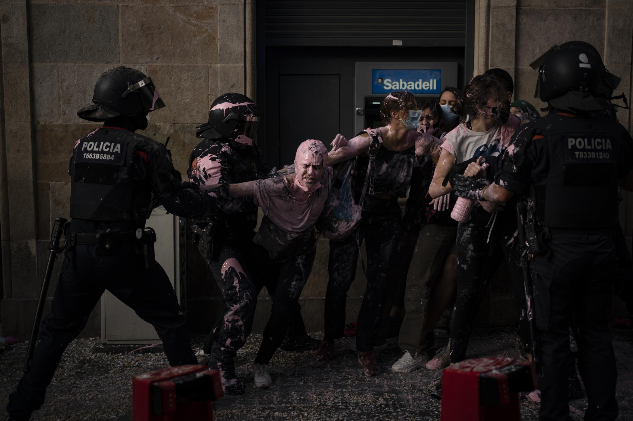 Riot police officers clash with protestors as they try to stop the eviction of Maite Mendibil, 58, from her apartment in Barcelona, Spain. Thursday, Oct. 1, 2020. Maite, has being accused of non-payment of a month's rent in 2015. The eviction was postponed with a help of anti-eviction activists that gathered outside the apartment block surrounded by riot police. (AP Photo/Joan Mateu)