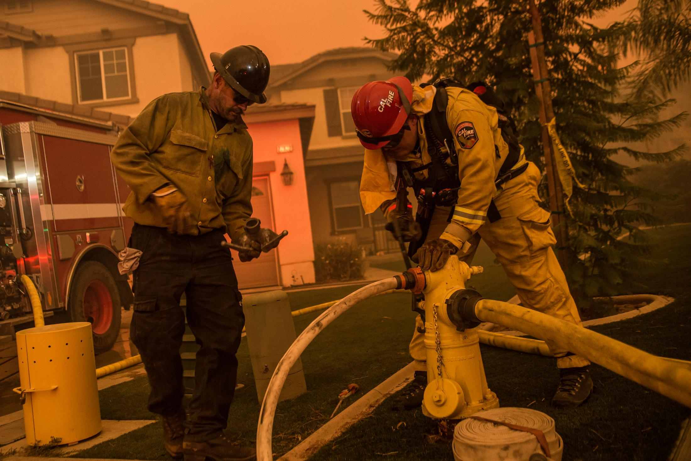 Two firefighters from different departments from Texas and California work together to attach hoses to a water source. The state of California faced its worst fire season in history. One of the worst fires located in Los Angeles and Ventura County named the Woolsey Fire. This wildfire burned; 96,949 acres and destroyed 1,643 structures. Three people reported to have died in the blaze, and over a quarter-million evacuated.