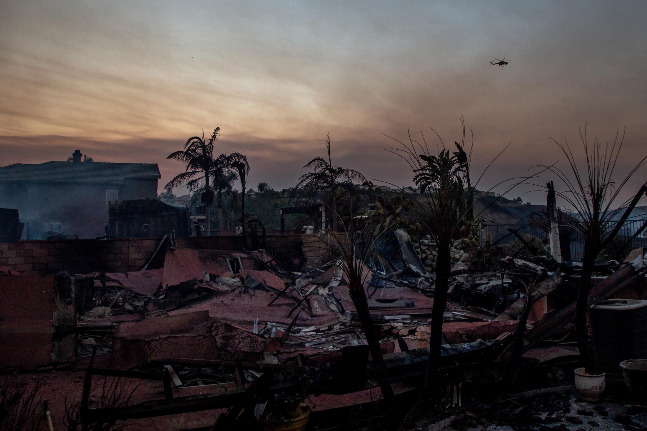 A helicopter flies over a neighborhood that has been destroyed by the wildfire. One thousand six hundred forty-three structures have turned to rubble and ash over a month of fire.