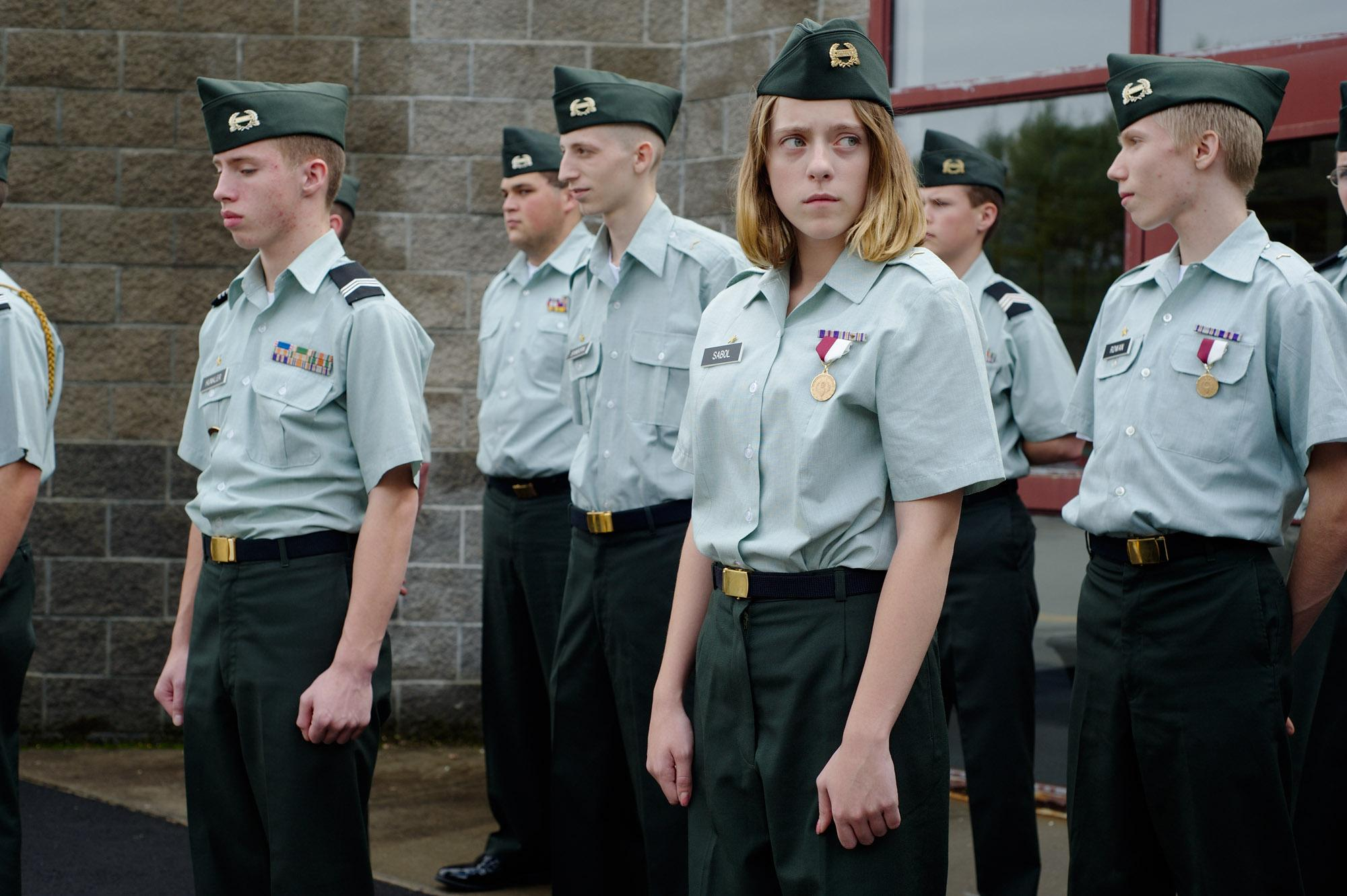 Cadets of the Junior Reserve Officers' Training Corps, JROTC, Wildcat Battalion of Fall Mountain Regional High School stand at attention during the inspection of their Class B uniform, which is used for less formal events or when it's warm. Many students are from families with a military tradition, like Riley (right). Her parents are retired Marines, her father transferred to the Army, her grandfather fought in the Korean War. Langdon, New Hampshire, USA. October 2010.