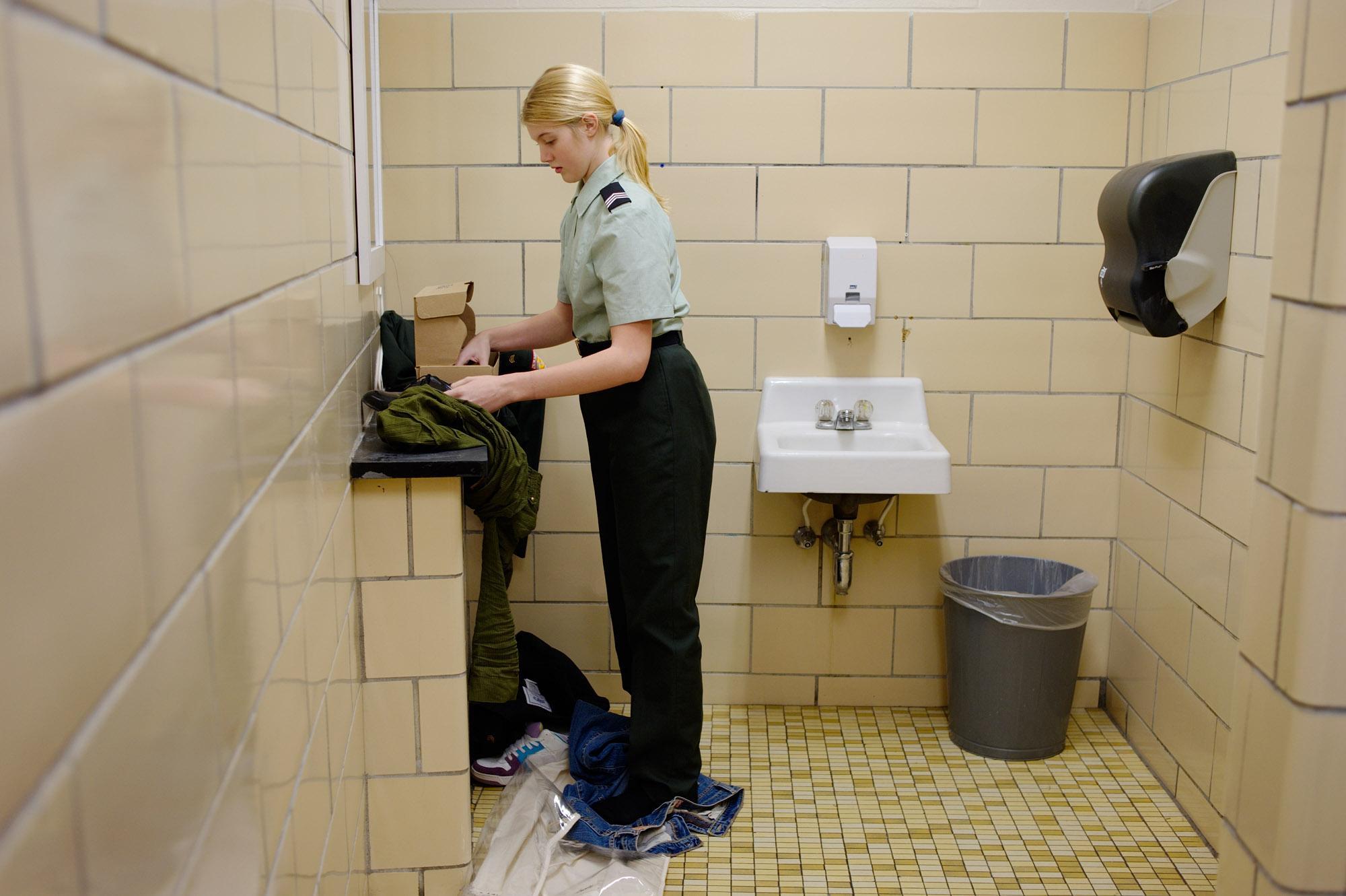 Jasmine changing into her Class B uniform in the school's bathroom. Langdon, New Hampshire, USA. December 2010.