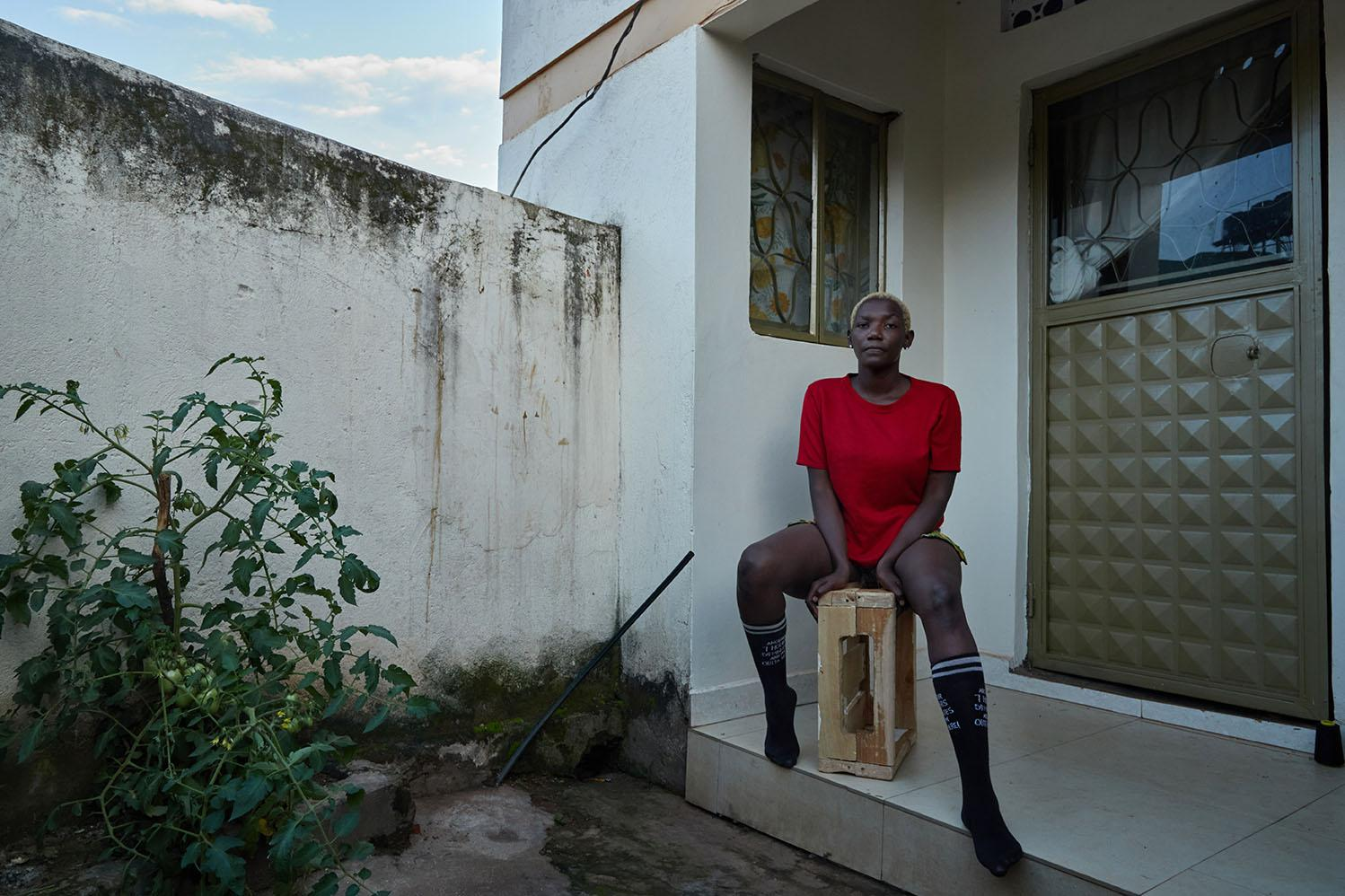 """Lillian Baraza (Bisexual), posses for a portrait outside her home in a suburb in Kampala. """"In this country and probably many others, you can't be kissing or holding hands of your partner if you are same-sex, they would burn you alive (laughs off). I really want to see better leadership where everyone is equal, and rights affect everyone the same way. Most importantly, the government needs to put in place medical services for the LGBTQ people, especially the gays and transgender because there is a lot of discrimination in health centers. Because I'm Bi, it is easy to get away with it, but I sympathize with the trans and gay people"""""""