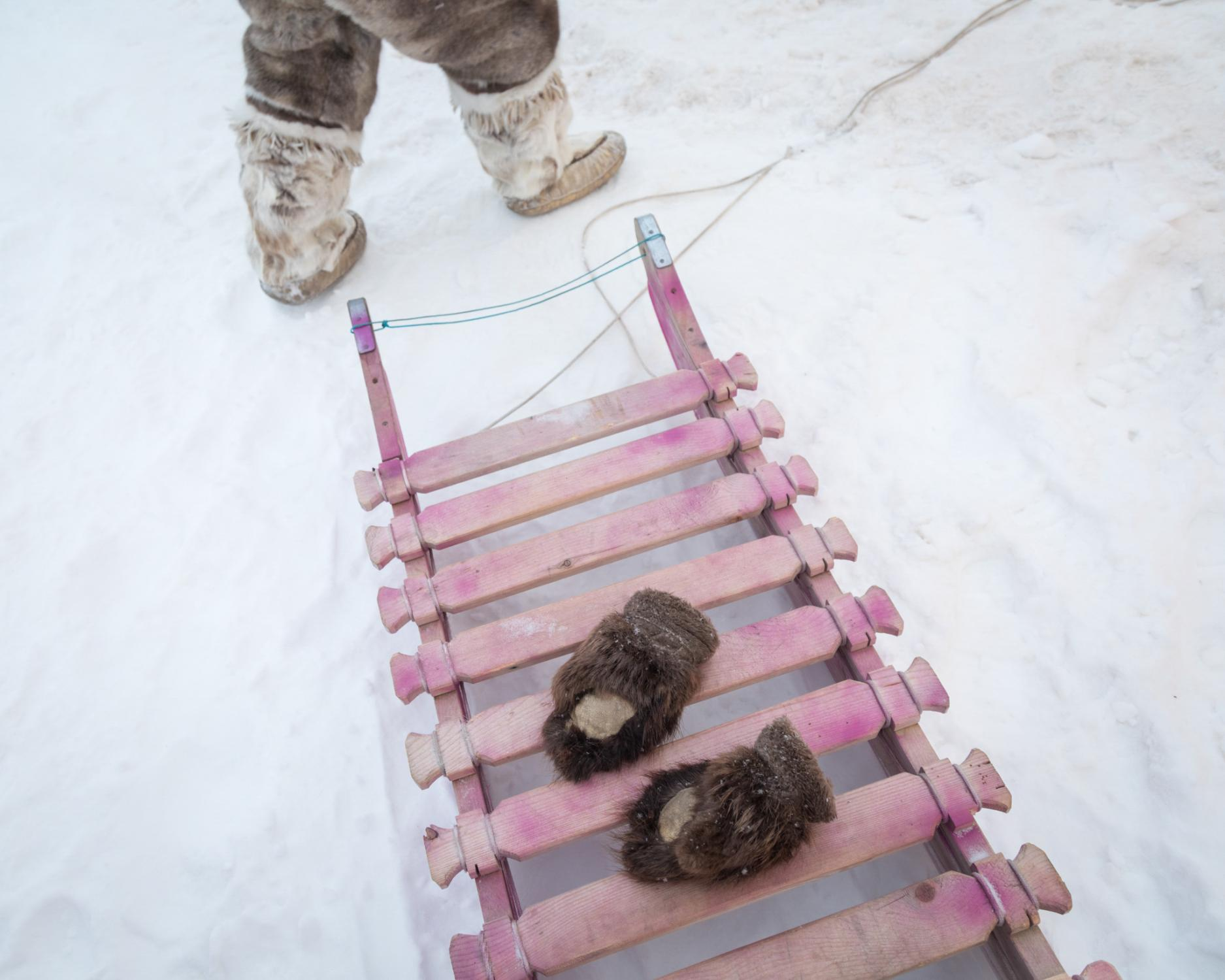 Alana Enoogoo, 6, leaves her mittens on her family's pink qamutik, or traditional sled — a miniature version of the one she and her family have pulled by snowmobile for 9 hours to reach their camp at a fishing lake. As well as being a fun toy, the sled will be used to haul rocks to hold down the family's tent.