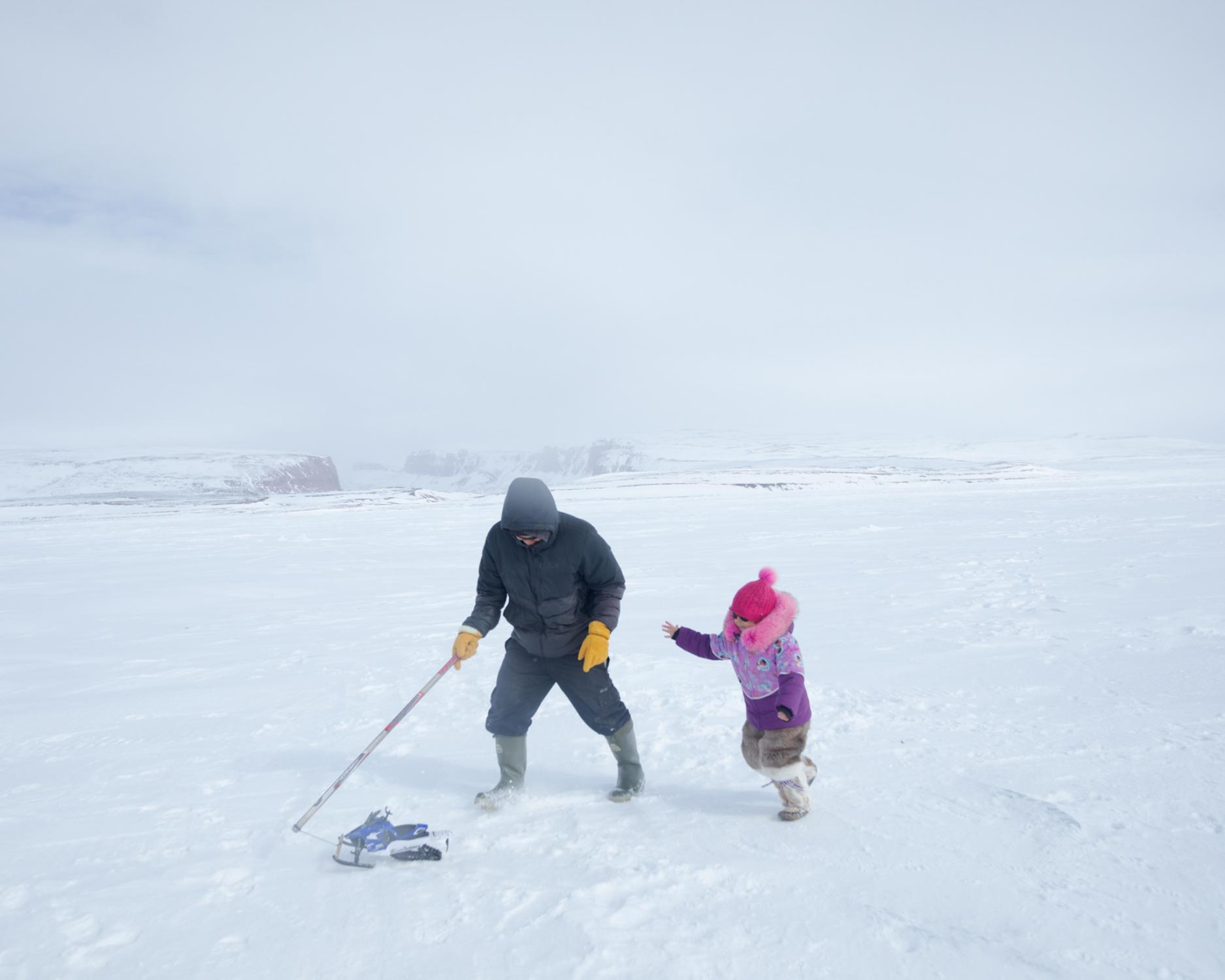 Darcy Enoogoo pulls a toy snowmobile across the sea ice for his daughter, Alana, during a tea break in their nine-hour snowmobile journey to a lake for Arctic Bay's annual Fishing Derby.