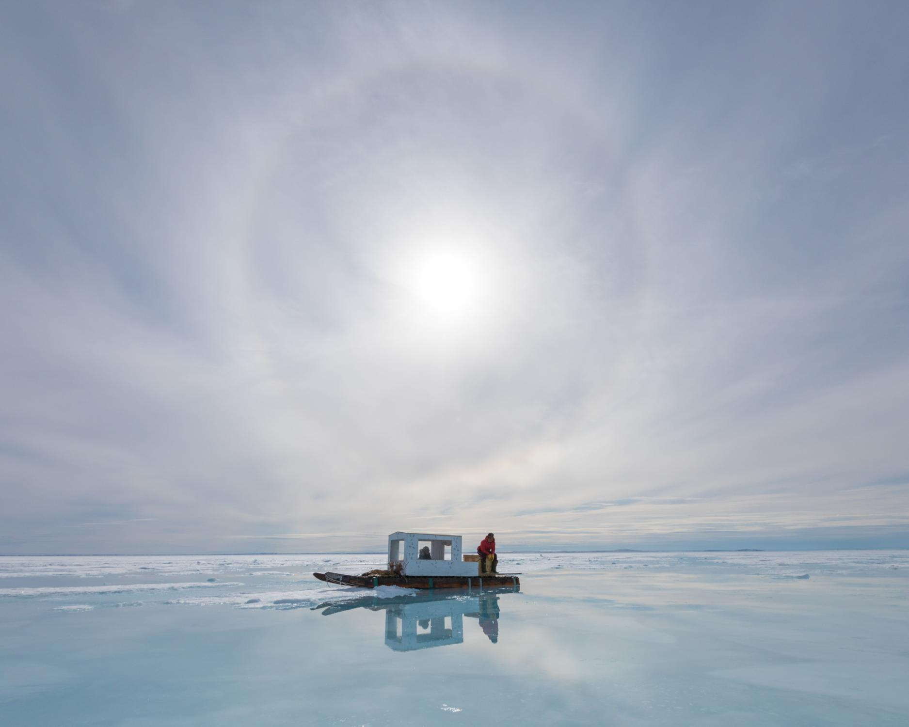 As a sun halo reflects off the sea ice, Owen Willie, 18, waits with his mother Darlene on their family's qamutik during a seal-hunting trip. Ringed seals, which each have a network of breathing holes in the surface of the sea ice, are sensitive to noise - any footsteps too near to a breathing hole can scare them away.