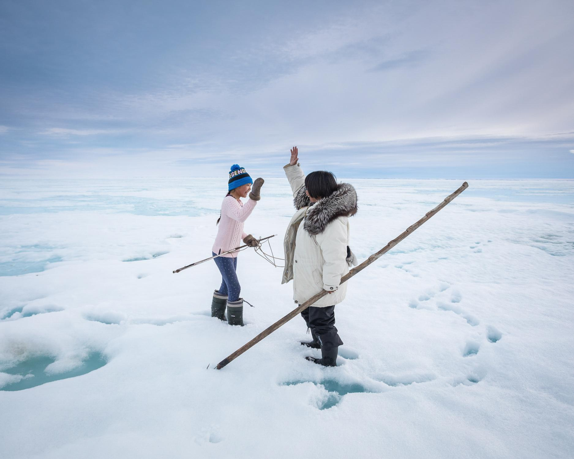 Celebrating the catch of her first seal, Horizon Willie, 10, gets a high-five from her aunt Leesie Naqitarvik, on the sea ice near their camp at Nuvukutaak. Leesie had traveled from her home in Ottawa to join her extended family for a camping trip to ancestral hunting grounds, where her parents shared their deep knowledge of the land.
