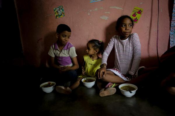 "CARACAS, VENEZUELA - APRIL 12: Children of Barrio Unión Sector Las Casitas eat soup prepared and donated by Alto Restaurant in the house of a neighbor on April 12, 2019 in Caracas, Venezuela. Local NGOs offer food to those in need, especially elderly people and children. ""Barriga Llena Corazón Contento"" Foundation has been supporting a nursing home and two soup kitchens in the community of Mesuca, Petare for more than three years. There are five Restaurants that collaborate preparing food from Monday to Friday. Each restaurant has its own recipe but all are made based on instructions from a nutritionist. Political and economic crisis has triggered a food emergency in Venezuela. Most supermarkets and shops do not offer a wide variety and amount of food and goods due to the shortage that affects the country. To struggle with semi empty shelves, Venezuelans have to navigate street stalls and vendors to get eggs, corn and wheat flour and rice which are the basis of the Venezuelan diet. According to the 2018 survey on life conditions ENCOVI, conducted by three local universities, 89% of people consider their incomes are not enough to afford a proper diet. Six out of 10 said they had gone to bed hungry because they did not have the money to buy food. International Monetary Found estimates a 10 million percent inflation for Venezuela in 2019 with skyrocketing rises in the price of food and goods, increasing the number of Venezuelans unable to access to a healthy nutrition. According to FAO Early Action on Food Security report 2019, Venezuela is in alert due to food insecurity and has no consistent humanitarian response plan. (Photo by Eva Marie Uzcategui/Getty Images)"