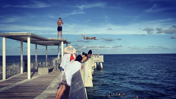 A man jumps into the ocean at South Pointe Pier in South Beach, Florida, U.S., July 10, 2019. Eva Marie Uzcategui
