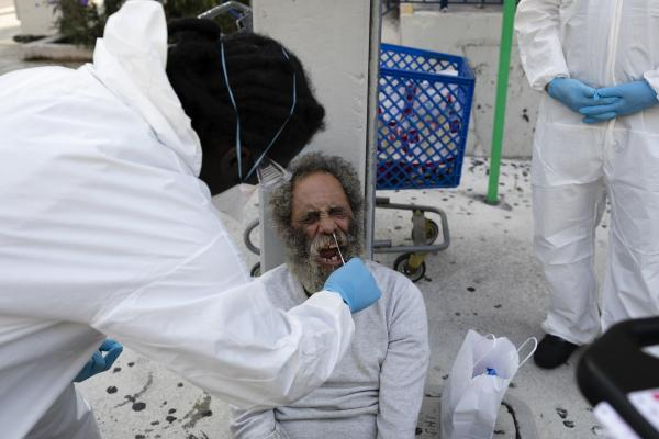 A worker of Miami-Dade County Homeless Trust takes a sampler test to a homeless for coronavirus disease (COVID-19) in Downtown Miami on April 16, 2020. Eva Marie UZCATEGUI