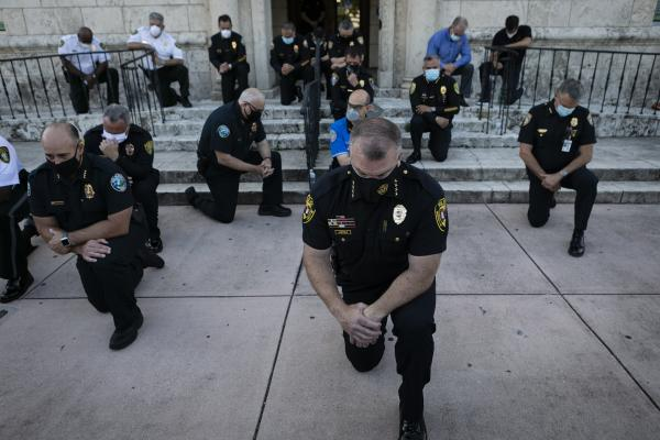 Police officers kneel during a rally in response to the recent death of George Floyd in Coral Gables, Florida on May 30, 2020. Eva Marie UZCATEGUI