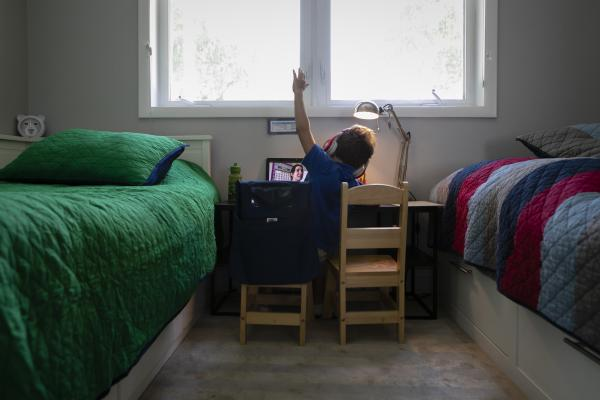 A student raises his hand while he is attending online distance learning from home in Miami, Florida, U.S., on Thursday, Sep. 03, 2020. Photographer: Eva Marie Uzcategui/Bloomberg
