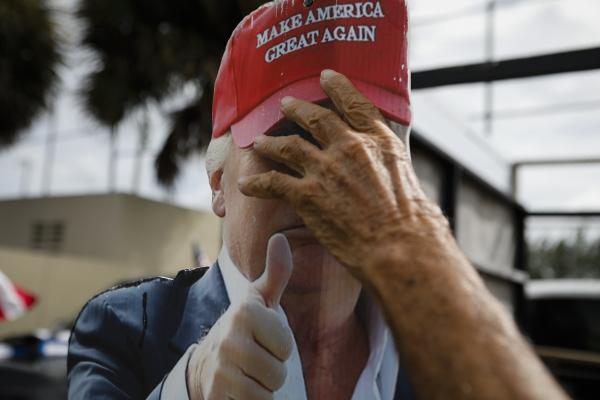 A hand holds a placard depicting U.S. President Donald Trump's face at John F. Kennedy Public Library in Hialeah, Florida on October 19, 2020. Eva Marie UZCATEGUI