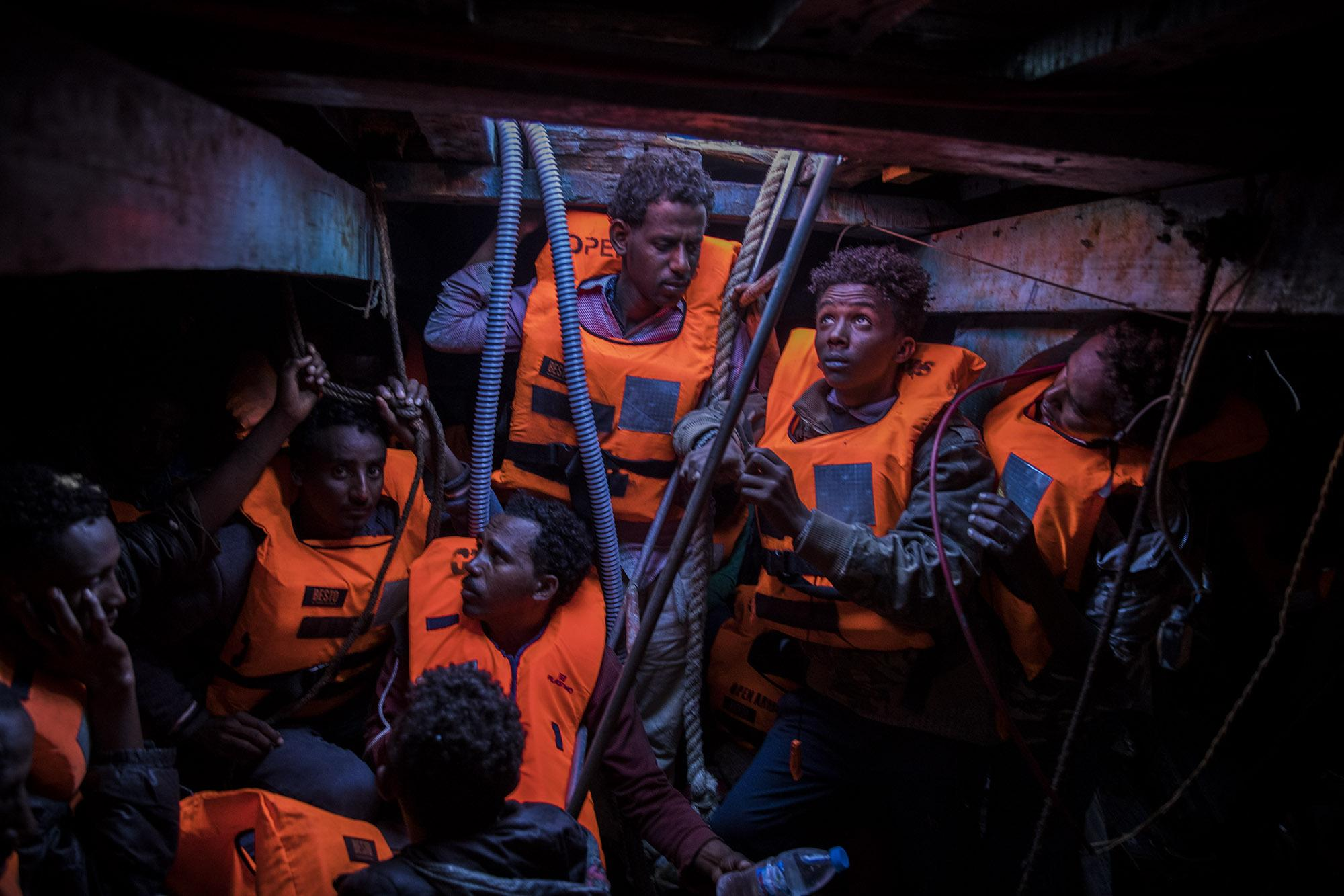 Men from Eritrea wait inside the lower deck of an overcrowded and drifting wooden boat to be rescued by aid workers of the Spanish NGO Open Arms, as they were trying to leave the Libyan coast and reach European soil with 500 other migrants. One of the babies on board had already died when the rescuers arrived, a young man and one more baby passed away during the rescue operation, 34 miles north of Kasr-El-Karabulli, Libya, Tuesday Jan. 16, 2018. (© Santi Palacios)