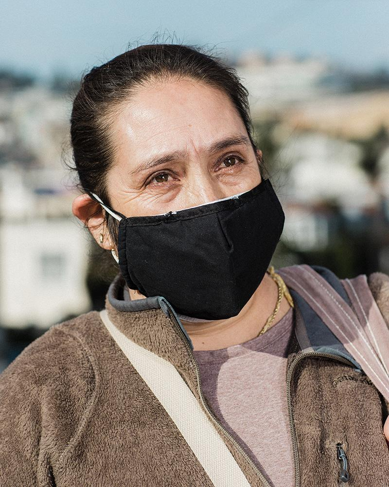 Maria Teresa Palacio stands for a portrait after waiting in line to receive food aid and just before hustling to the bus stop to a house cleaning job. Maria has lost most of her clients since the pandemic. Wednesday, December 9, 2020
