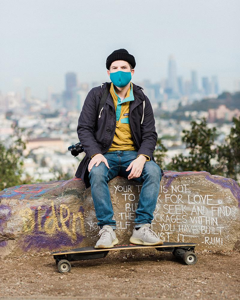 Micah Weiss, a freelance photographer, sits with his camera and electric skateboard at Bernal Heights on Tuesday, December 15, 2020.