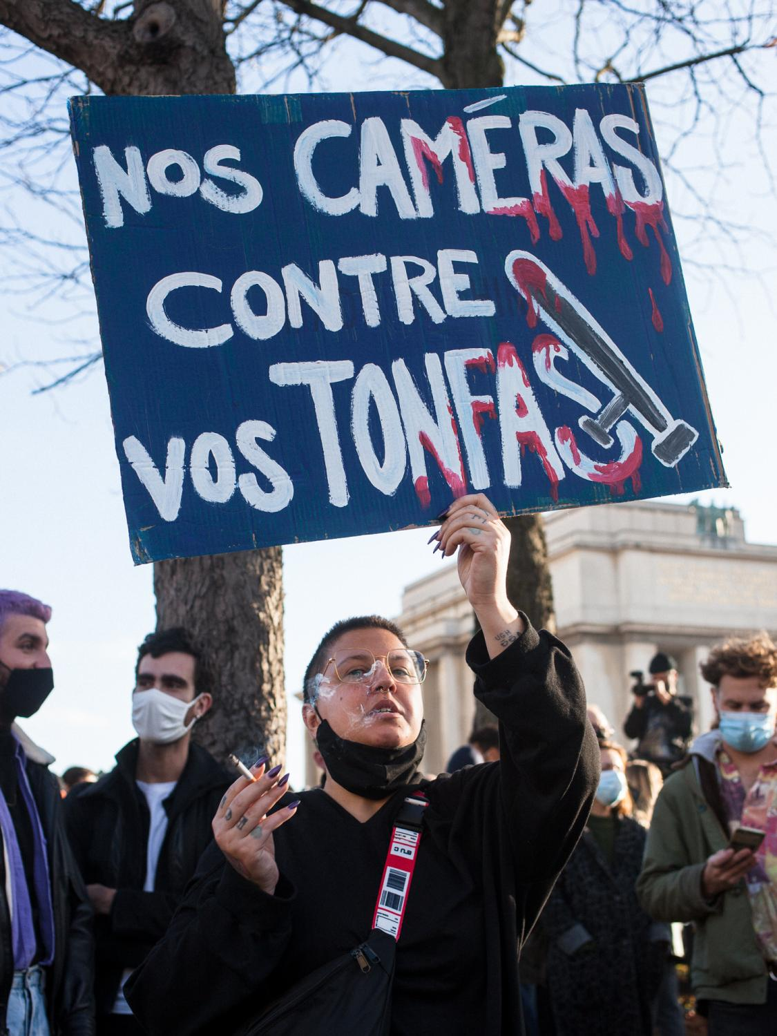 """In front of the barricaded Human Rights Square a woman holds a banner reading """"Nos caméras contre vos tonfas"""" (Our cameras against your batons). Rally against the controversial so called """"Sécurité Globale"""" (Global Security) bill. Trocadero Square, Paris, France, the 21st of November 2020."""
