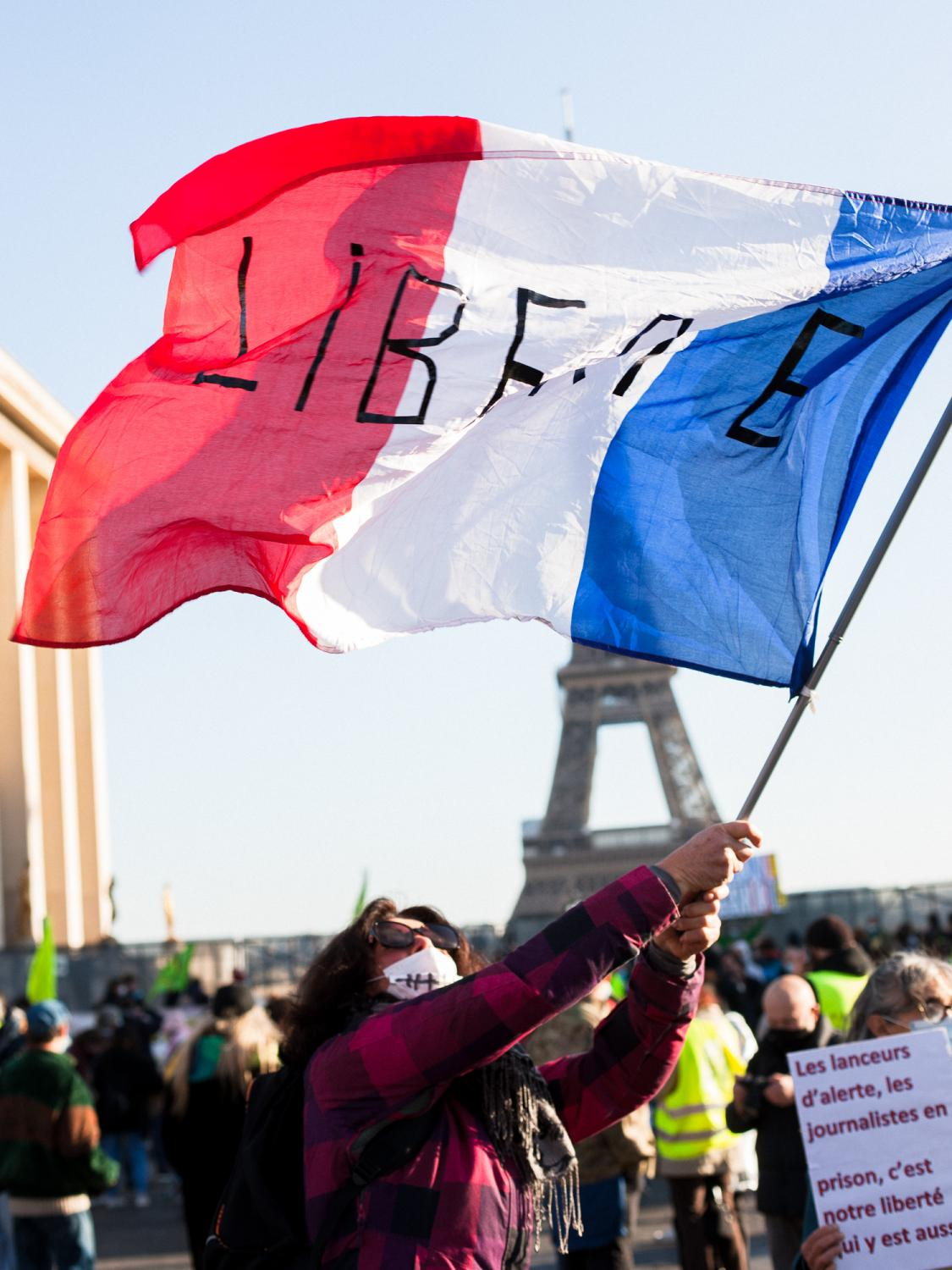 """In front of the barricaded Human Rights Square a woman waves a French flag reading """"Liberté"""" (freedom). Rally against the controversial so called """"Sécurité Globale"""" (Global Security) bill. Trocadero Square, Paris, France, the 21st of November 2020."""