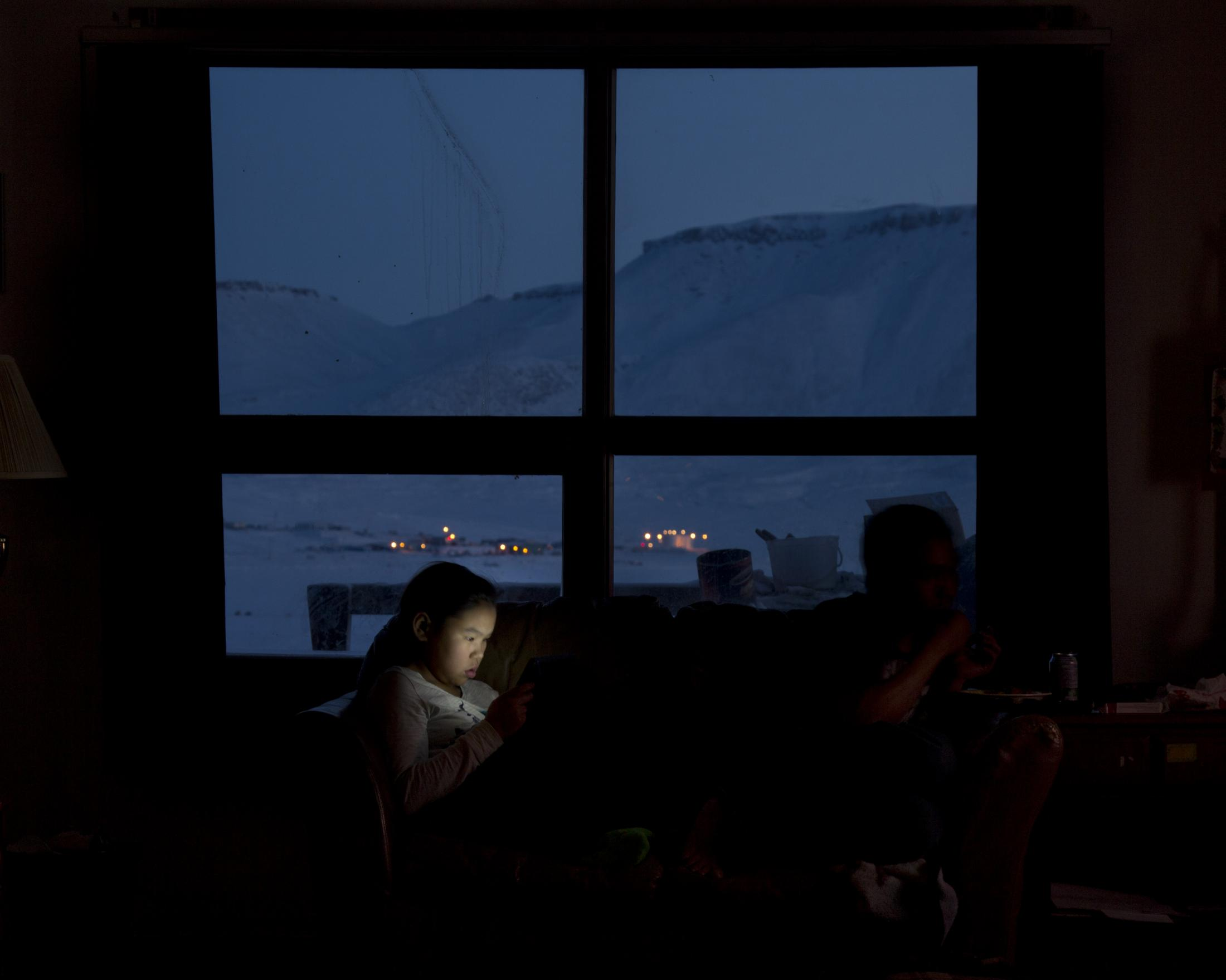 Sipporah Ejangiaq, 12, plays on her iPad during a lunch break from school.