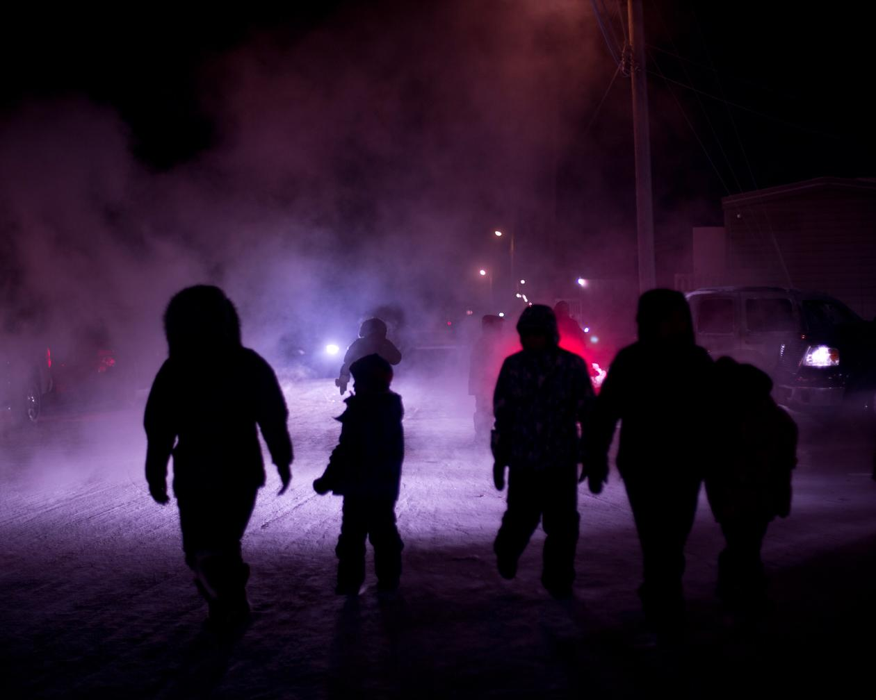On New Year's Eve, residents of Arctic Bay exit the community hall to watch the fireworks over the sea ice.